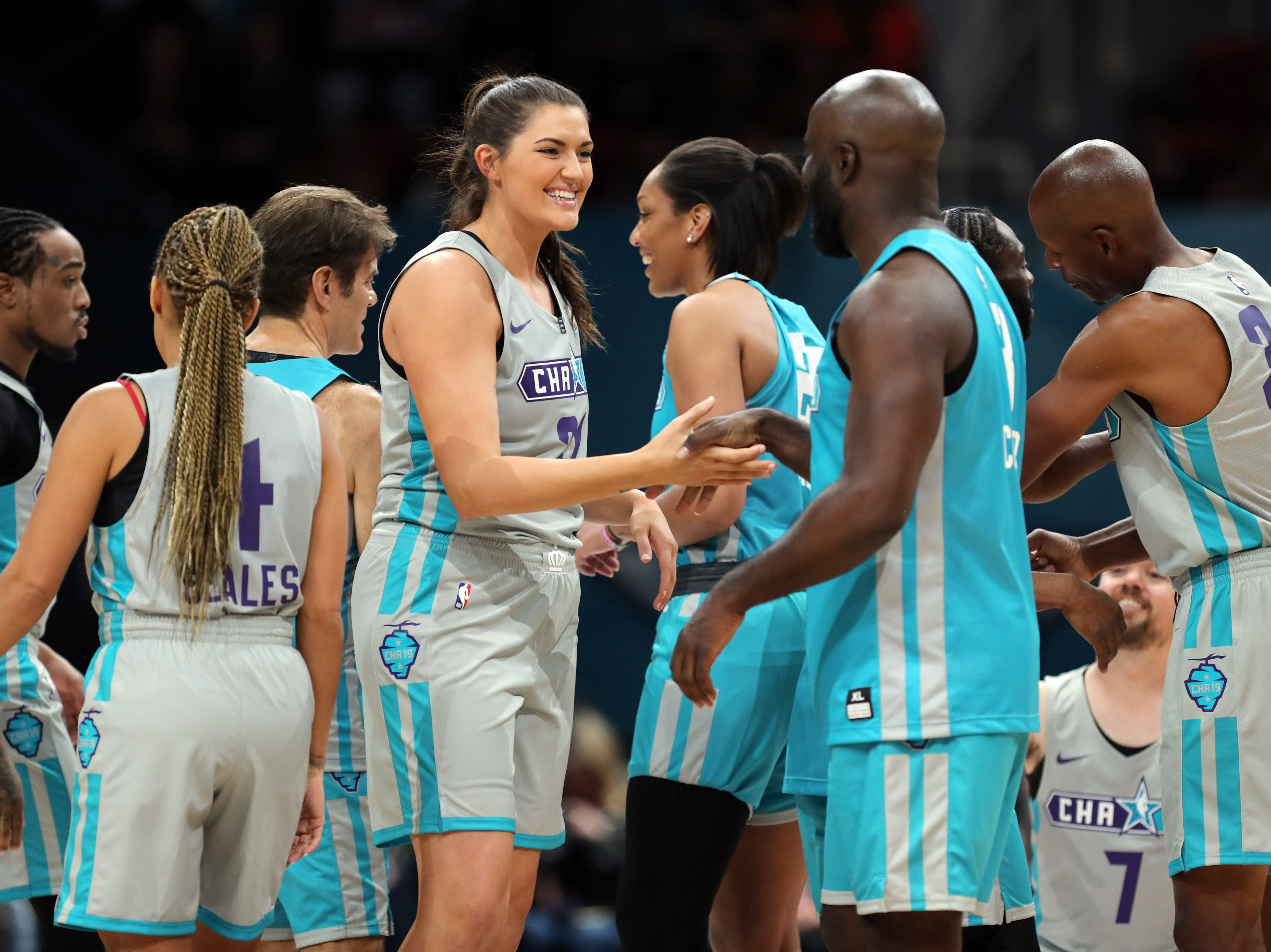 Stefanie Dolson shakes hands with Mike Colter before the Celebrity Game.