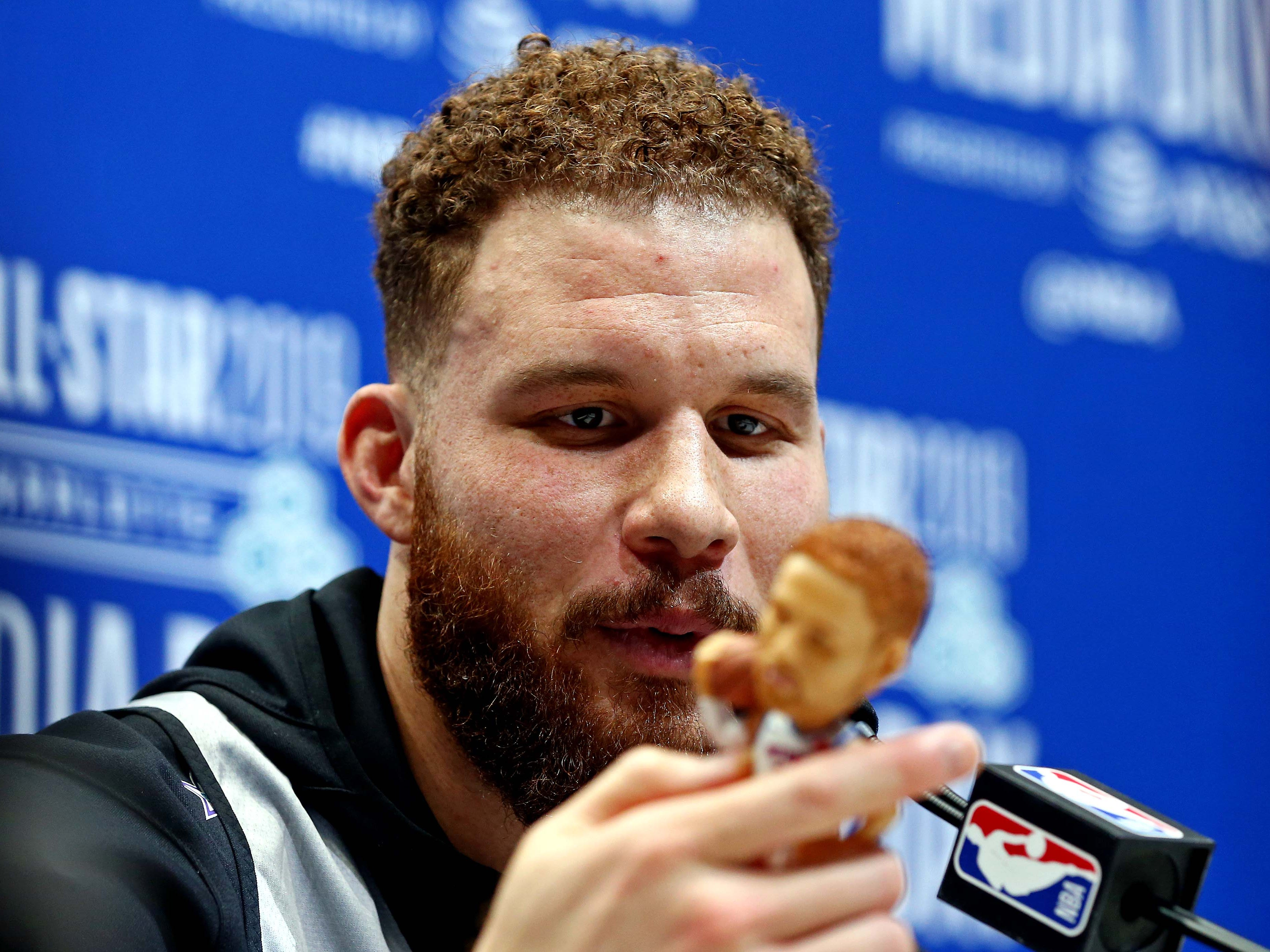 Blake Griffin looks at a bobblehead of himself during NBA All-Star Media Day.