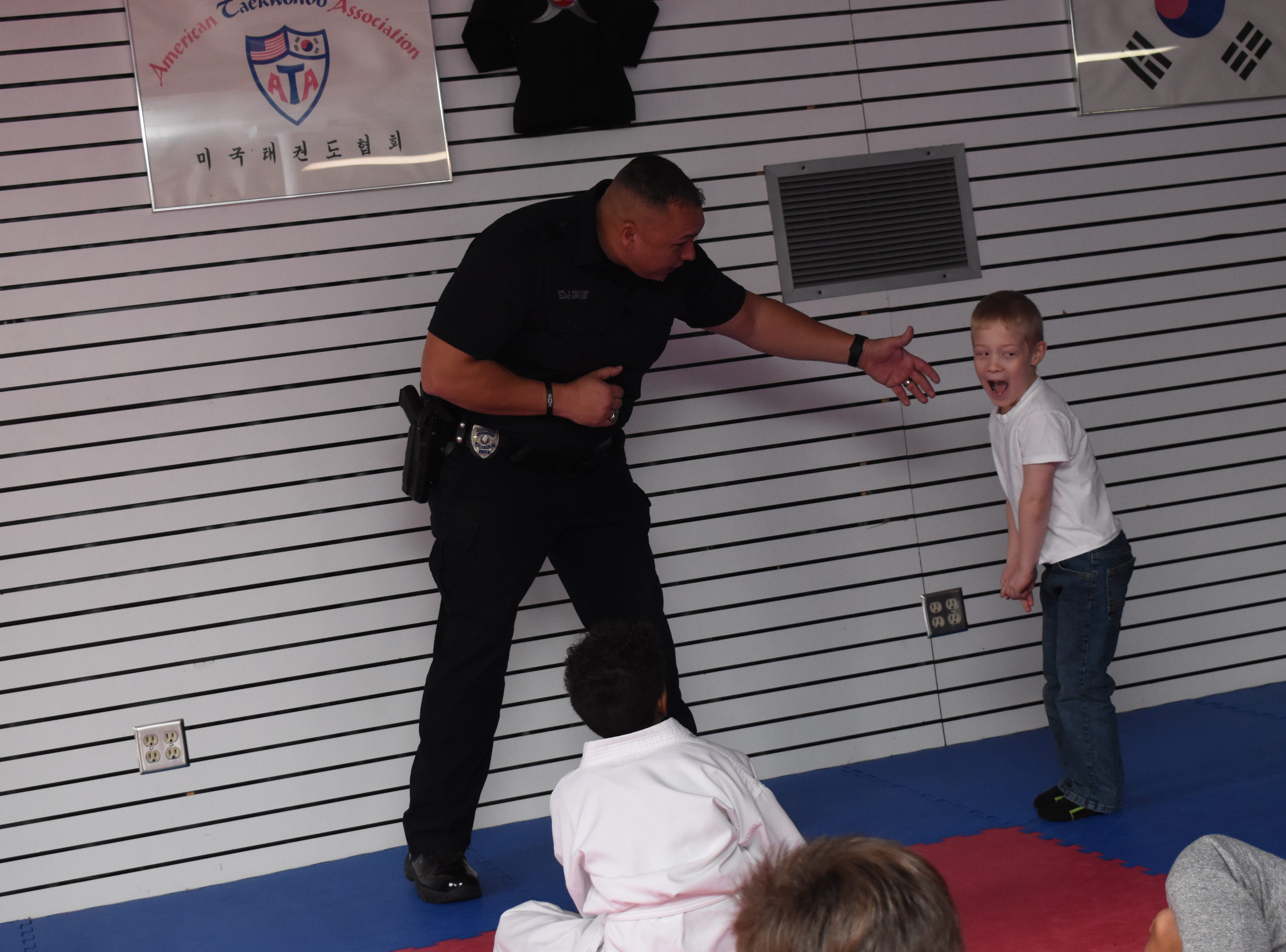 """Rapides DARE officer Vern Rennier (left) of the Alexandria Police Department pretends to grab Asher Goucher who yells and runs away. Master Rousseau's Taekwondo held a free """"Stranger Danger"""" defense class for children ages 7-12  Saturday, Feb. 16, 2019. Children were taught self-defense techniques to use if they to be grabbed by someone they did not know. They were advised to fight back and yell loudly. Rennier and Rapides DARE officer Derek Parker with the Pineville Police Department talked the children about protecting themselves."""