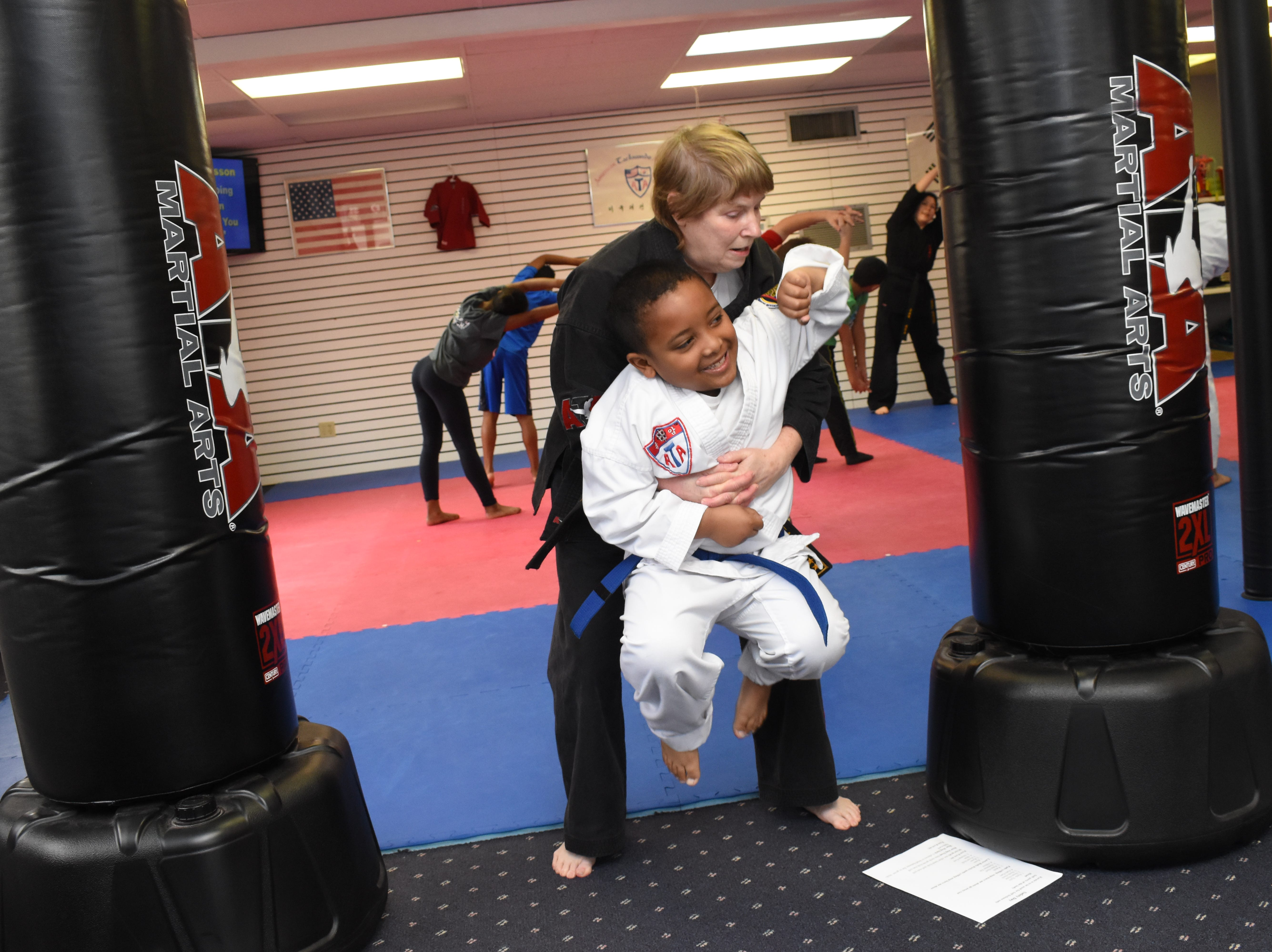 """Kaden Dunn (front) helps Carol Rousseau, owner of Master Rousseau's Taekwondo,with a demonstration on how to fight back if a stranger were to grab him from behind. A free """"Stranger Danger"""" defense class for children ages 7-12 was held Saturday, Feb. 16, 2019 at Master Rousseau's Taekwondo located on Jackson Street. Children were taught self-defense techniques to use if they to be grabbed by someone they did not know. They were advised to fight back and yell loudly. Also on hand to talk to the children were Rapides DARE officers Derek Parker with the Pineville Police Department and Vern Rennier with the Alexandria Police Department."""