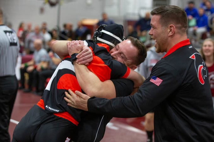 Kayla Gregory jumps into the arms of her coaches after pulling off a last minute pin in her 127 lbs South Region match against Manalapan's Angelina Vitola NJSIAA Girls Region Wrestling at Red Bank Regional High School in Red Bank NJ on February 17, 2019.