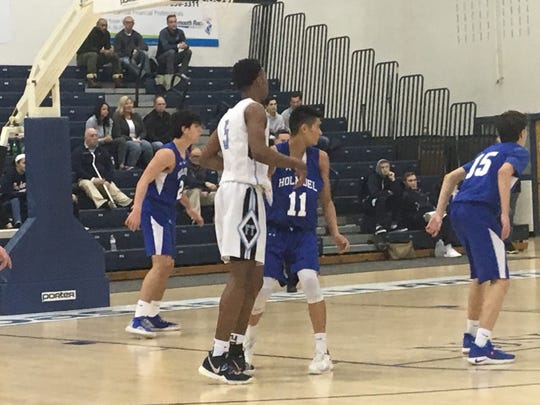 Freehold Township's Greg Billups (5) is guarded by Holmdel's Doug Chan (11) as a play is in progress during the SCT quarterfinal game on Feb. 17, 2019 at the RWJ Barnabas Health Arena.