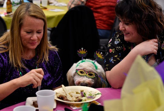 Kerri Kirby (left) and Kylie McQuade laugh at Kirby's dog Kalli, a golden doodle, during Saturday's Fur Ball at the Abilene Convention Center. The evening benefited Rescue the Animals and featured Mardi Gras-themed costume contests and dances.