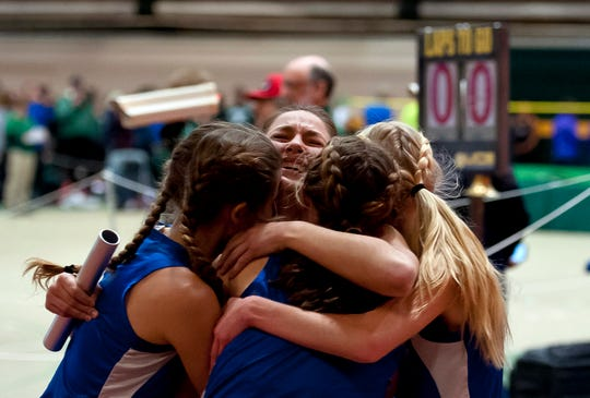 Missisquoi's Callie Parks, center, is mobbed by her teammates after running the final leg of their victorious 4x800 meter relay at the high school indoor track state championships at the University of Vermont on Saturday.