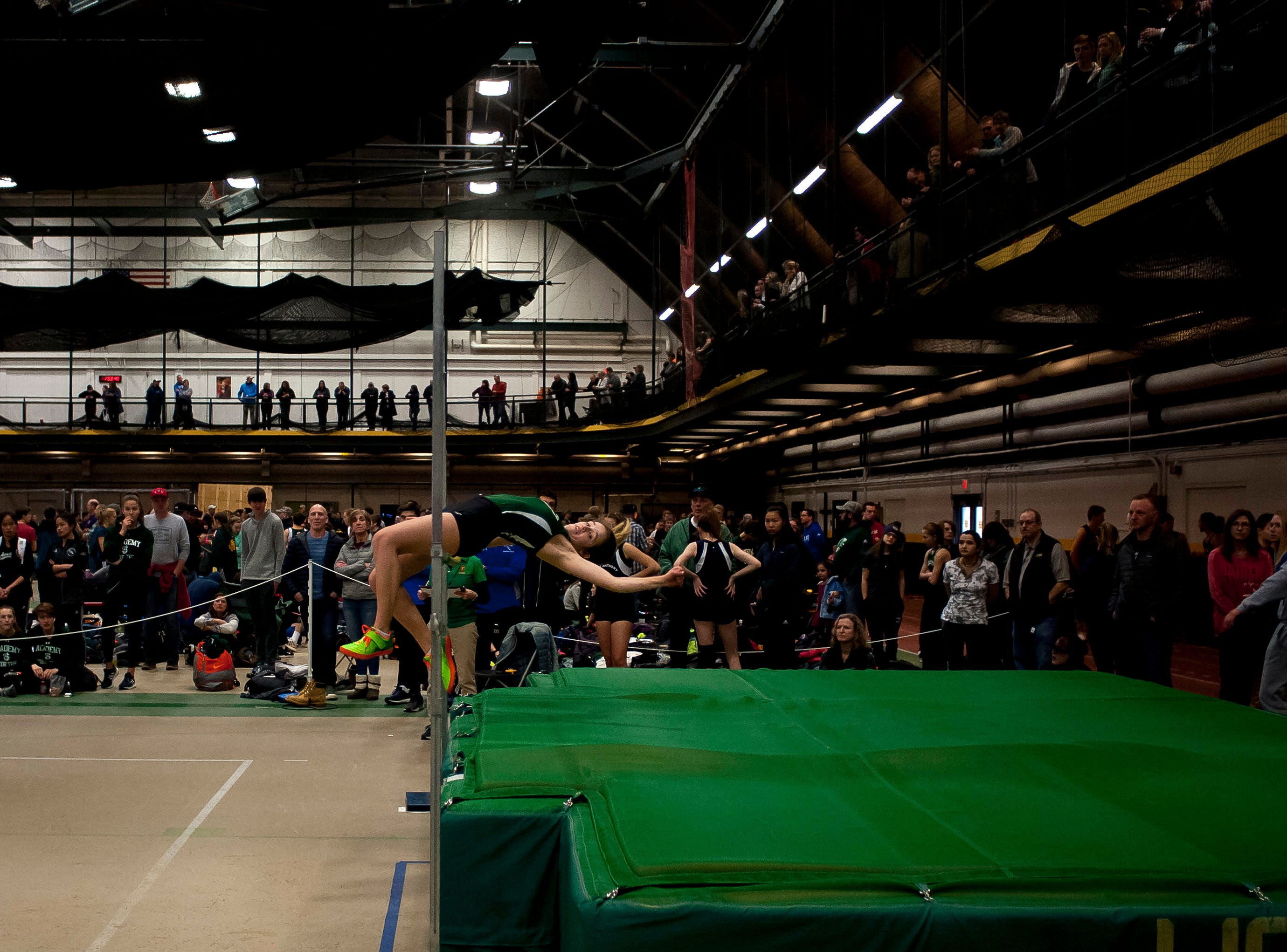 Spectators look on as St. Johnsbury's Isabella Bostic clears the bar in the high jump at the high school indoor track state championships at the University of Vermont on Saturday.