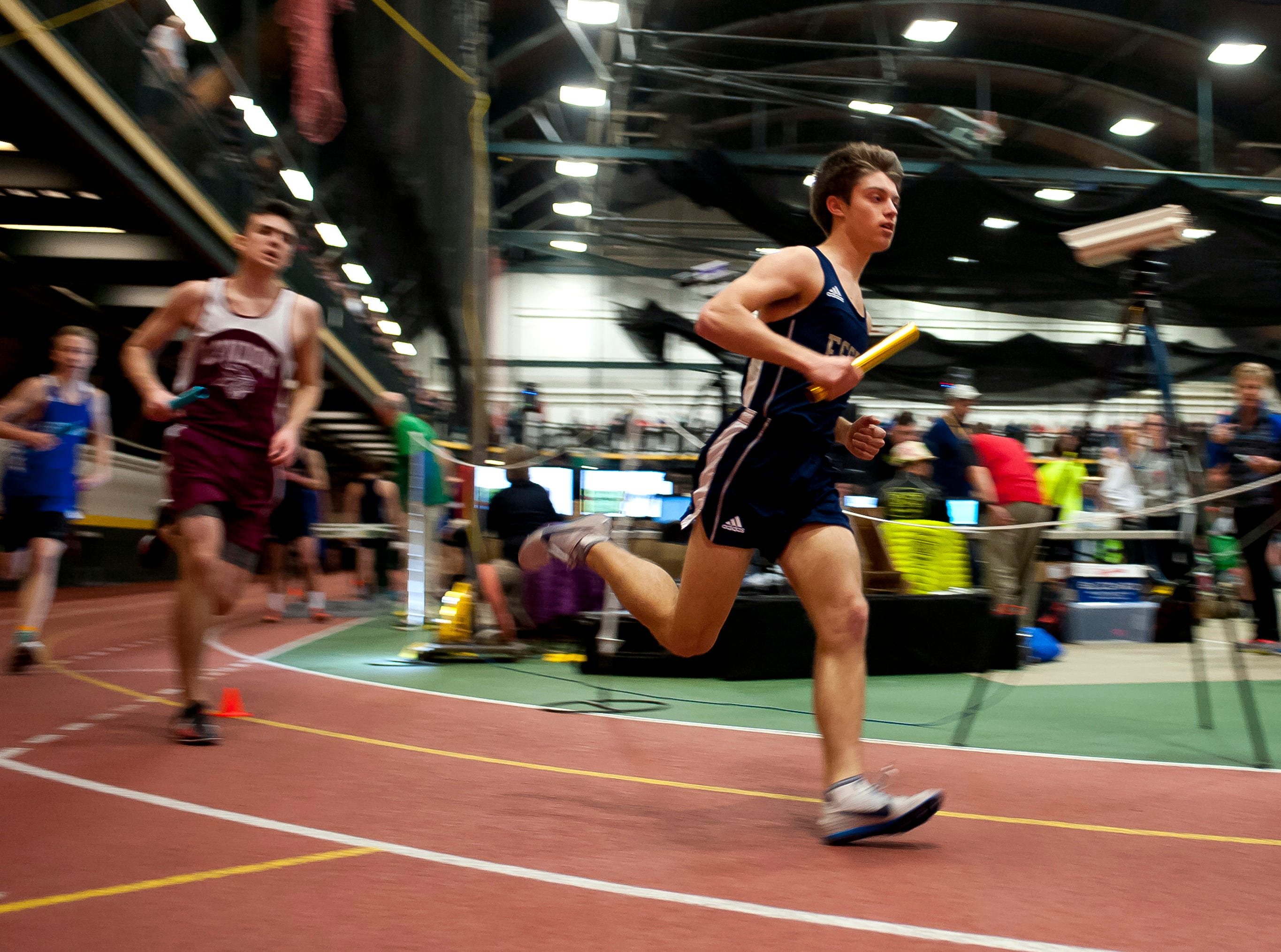 Essex's Brady Martisus, right, takes a corner in the boys 4x800 meter relay at the high school indoor track state championships at the University of Vermont on Saturday.