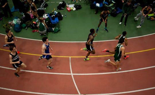 Runners take a turn in the boys 600 meters at the high school indoor track state championships at the University of Vermont on Saturday.
