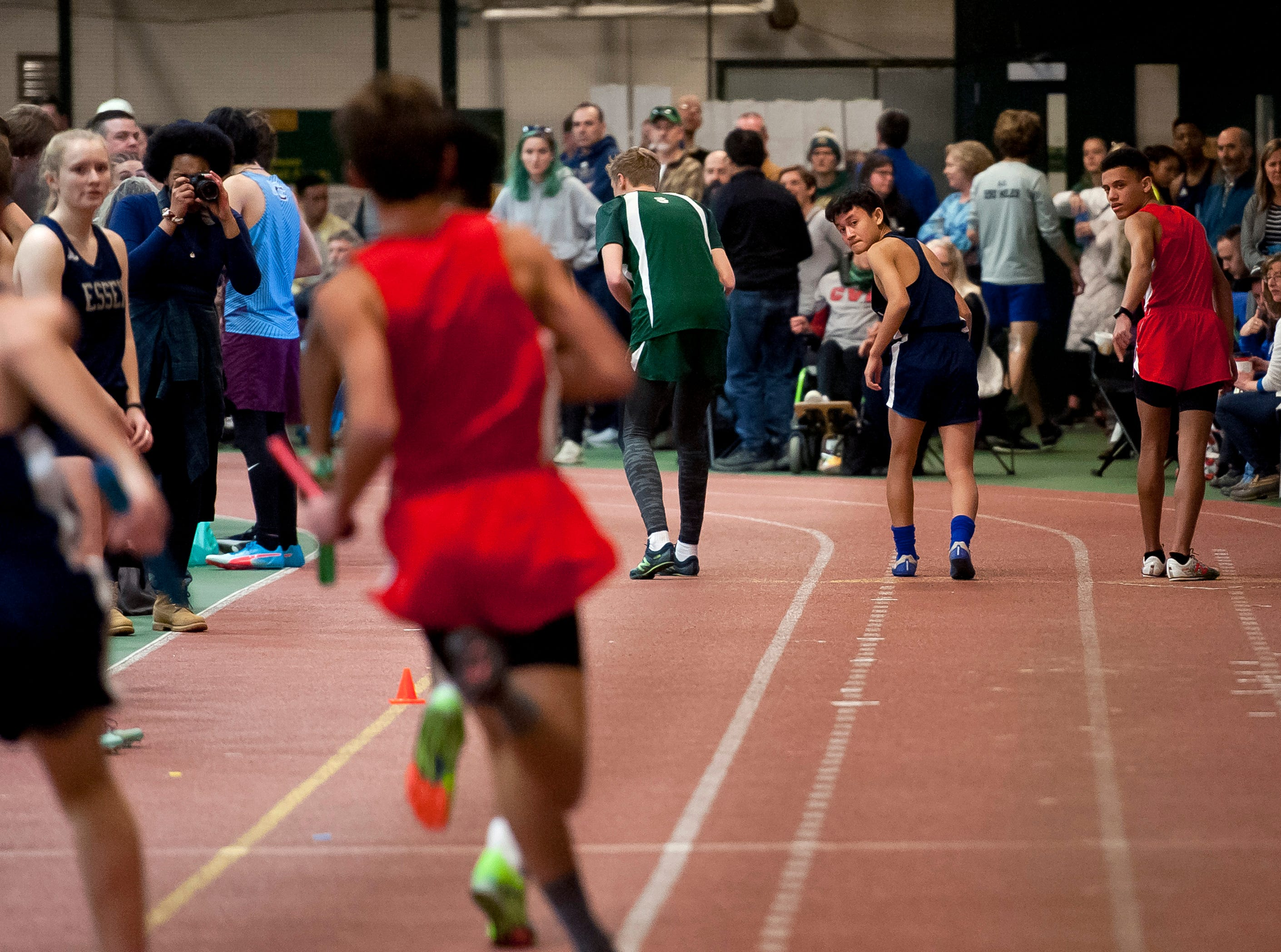 Runners look back for the baton handoff in the boys 4x200 meter relay at the high school indoor track state championships at the University of Vermont on Saturday.