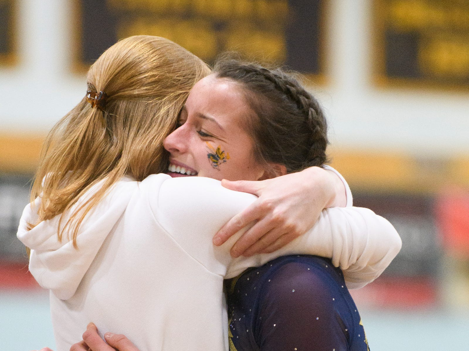 Essex's Abigael Gleason hugs a coach after her bar routine during the 2019 high school gymnastics championship at Essex High School on Saturday afternoon February 16, 2019 in Essex, Vermont.