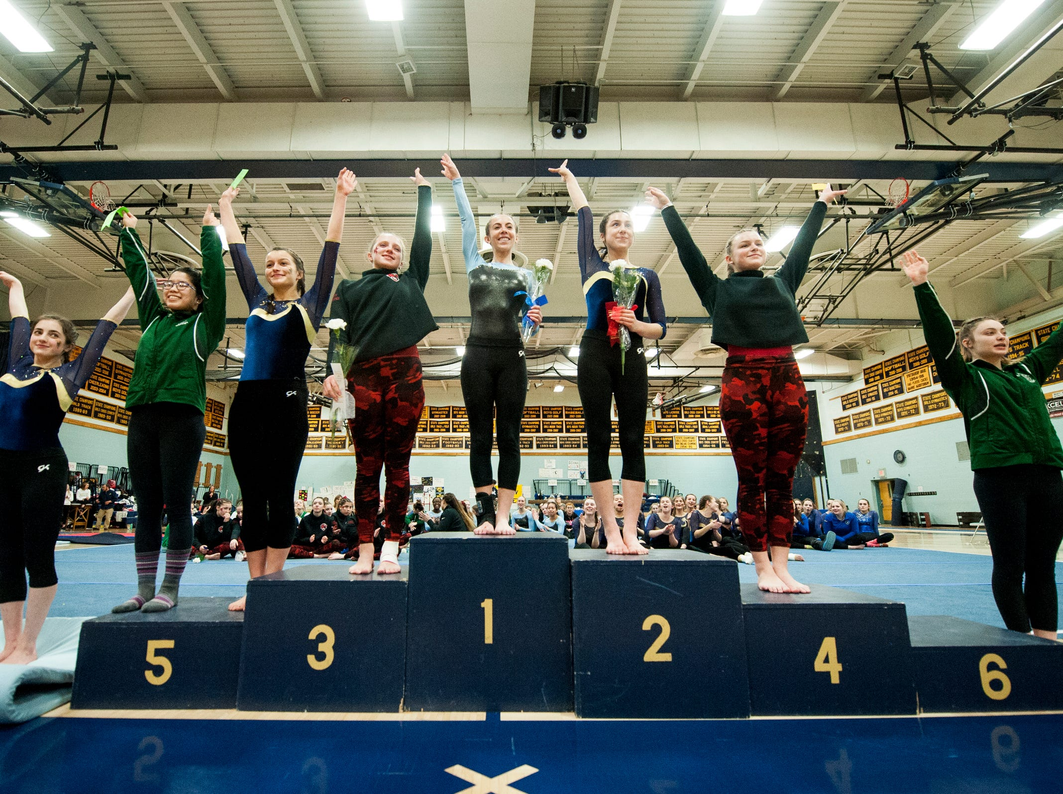 The Individual medal winners for overall performance wave to the crowd during the 2019 high school gymnastics championship at Essex High School on Saturday afternoon February 16, 2019 in Essex, Vermont.