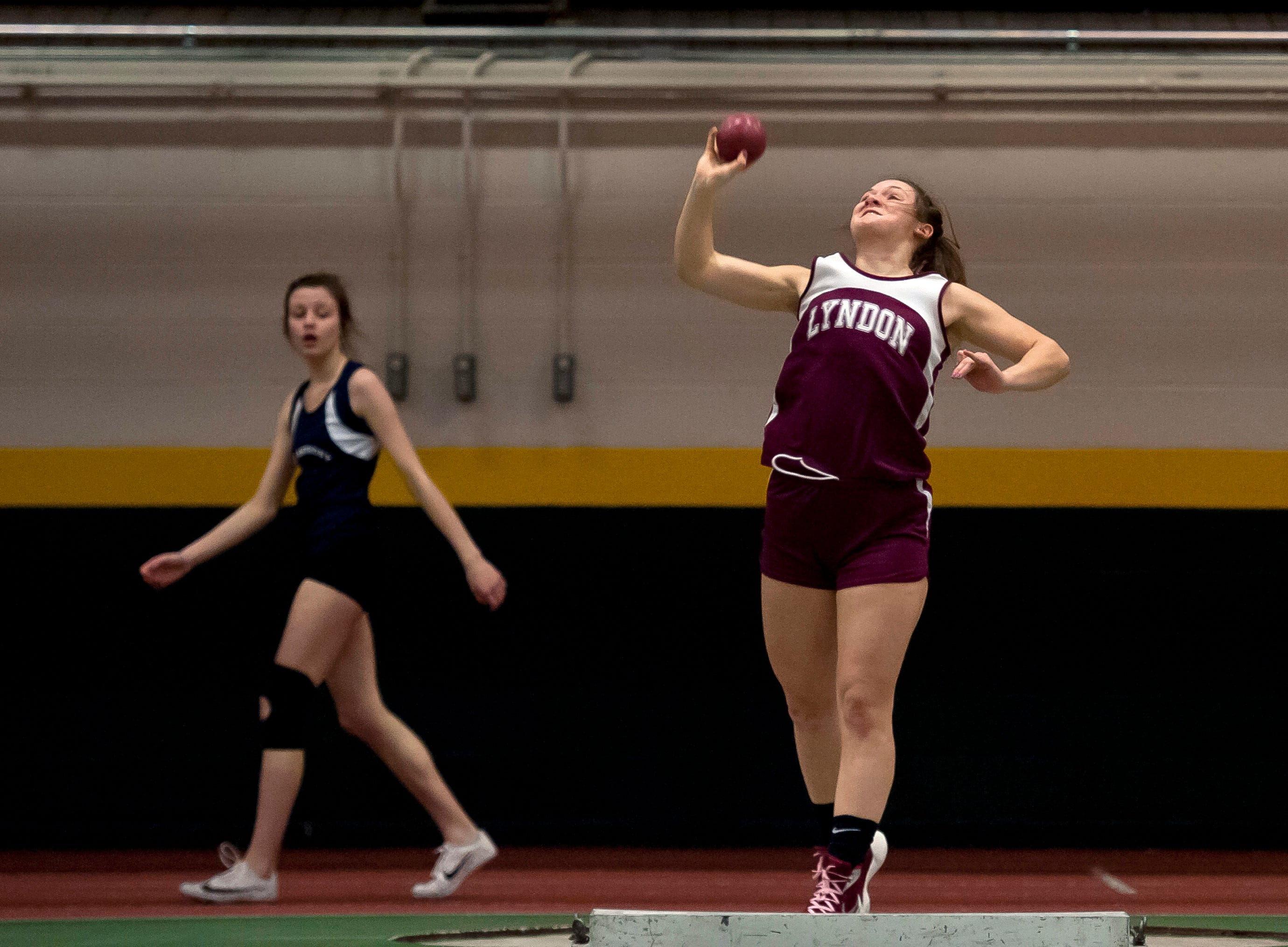 Lyndon's Camryn Heath , right, heaves the shot put at the high school indoor track state championships at the University of Vermont on Saturday.