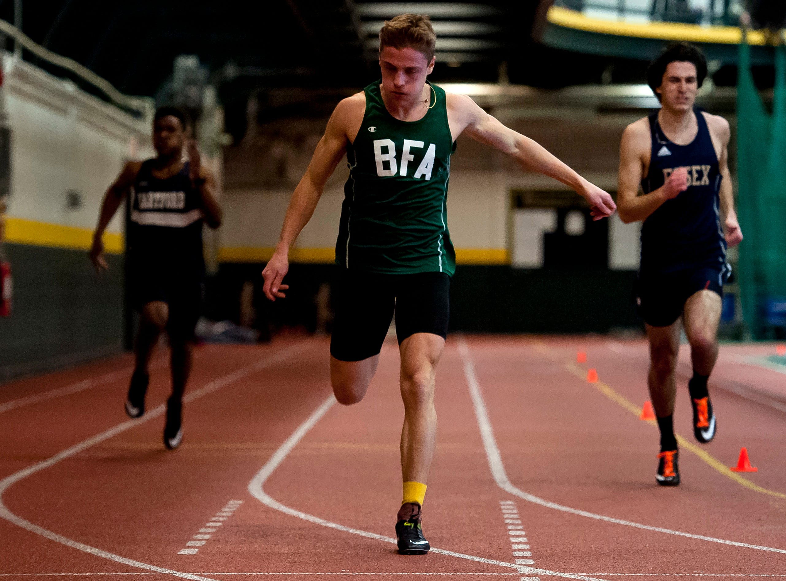 BFA-St. Albans Trey Poquette, center, hits the finish line to win the boys 300 meters at the high school indoor track state championships at the University of Vermont on Saturday.