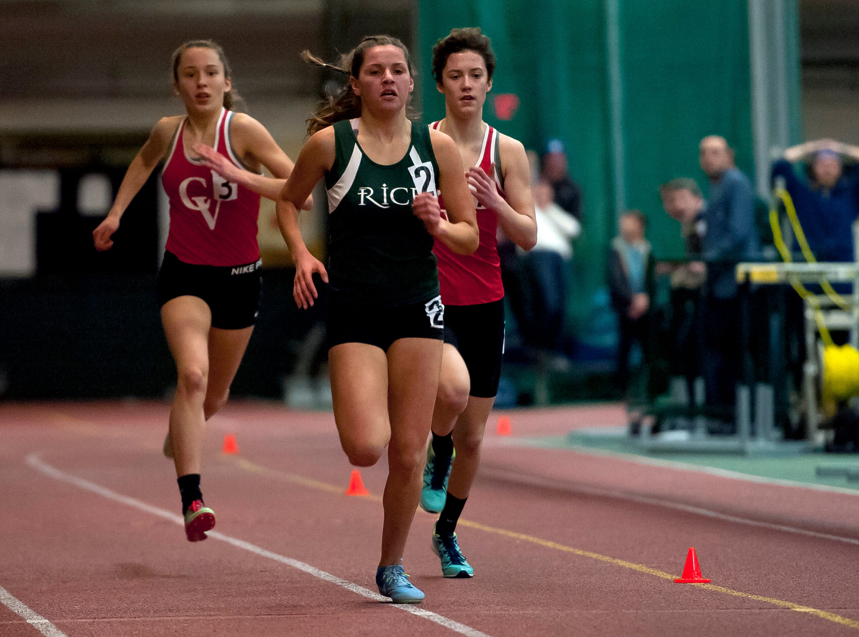 Rice's Emily Bloom, center, passes Champlain Valley's Ella Whitman and Alice Larson in the girls 1,500 meters at the high school indoor track state championships at the University of Vermont on Saturday.