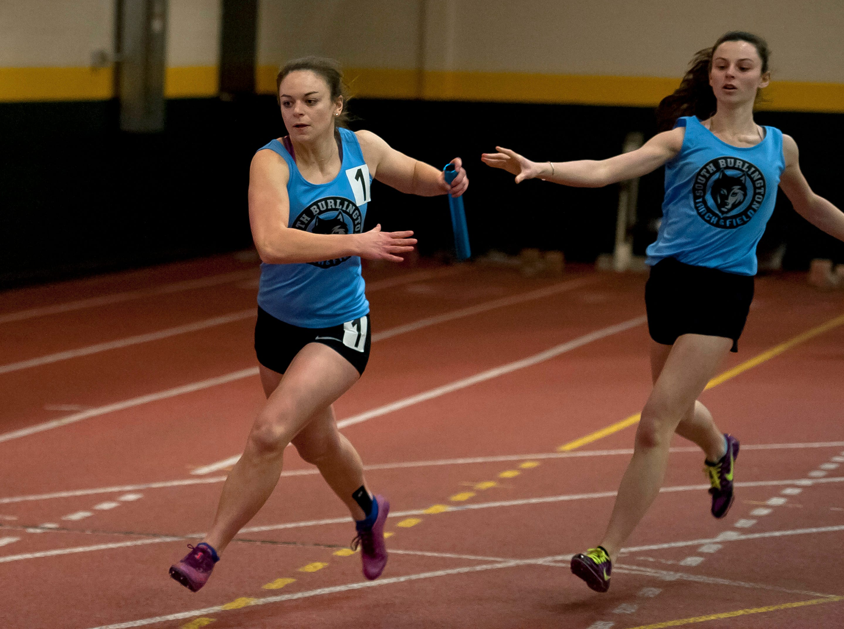 South Burlington's Cora Kakalec , left, takes the handoff from Sophia Thomas in the girls 4x200 meter relay at the high school indoor track state championships at the University of Vermont on Saturday.
