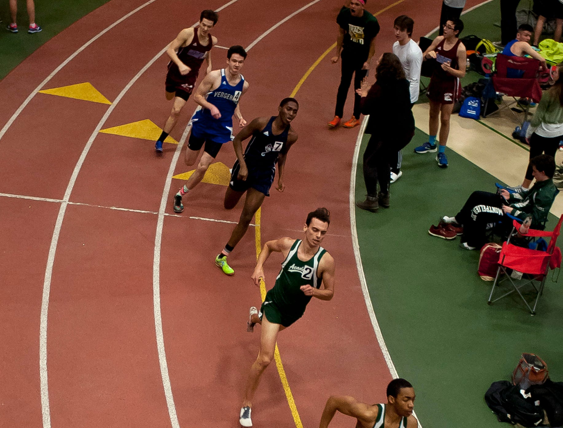 Runners round the first bend in the boys 600 meters at the high school indoor track state championships at the University of Vermont on Saturday.