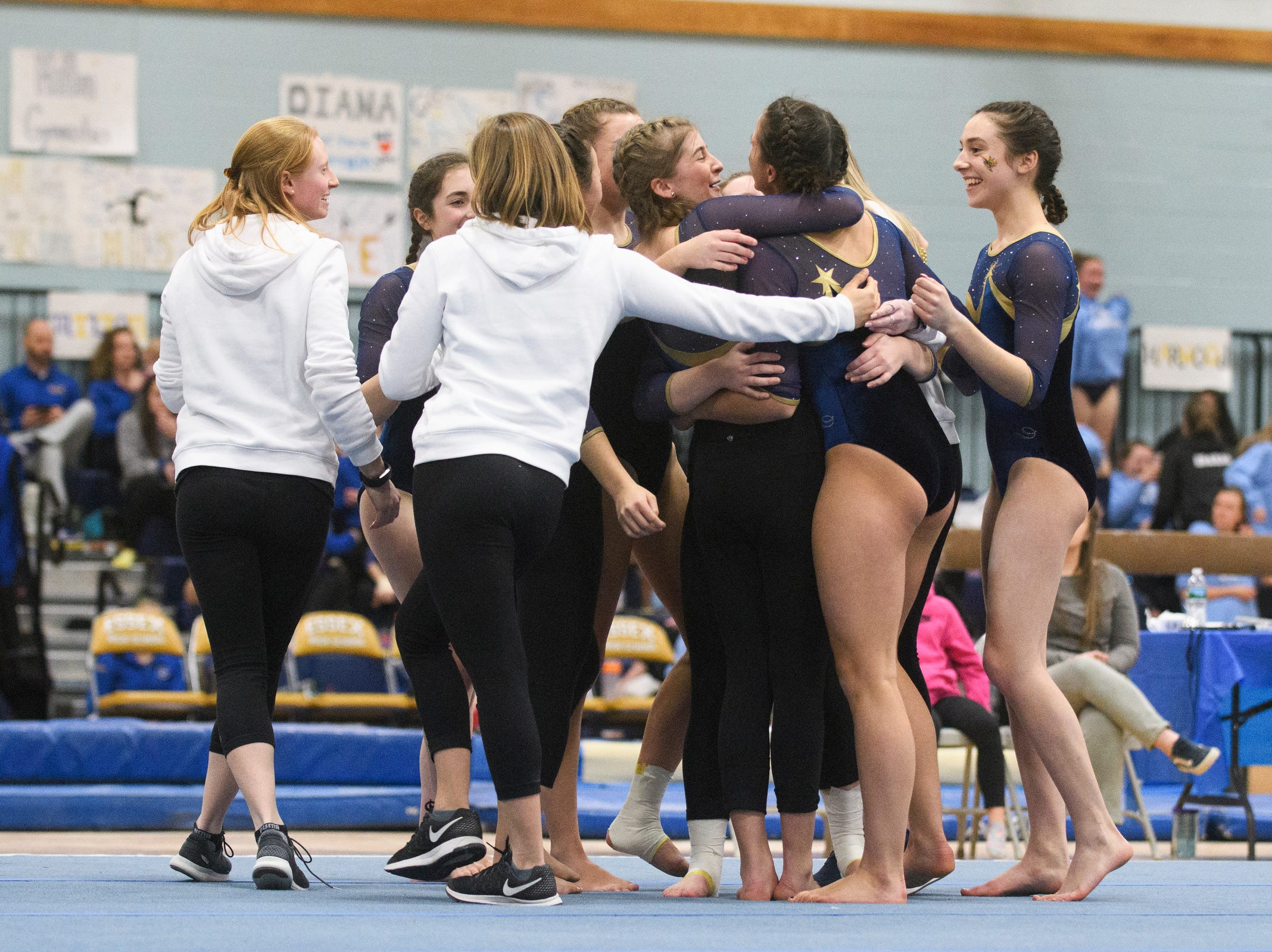 The Essex team hugs Abigail Gleason after her routine during the 2019 high school gymnastics championship at Essex High School on Saturday afternoon February 16, 2019 in Essex, Vermont.