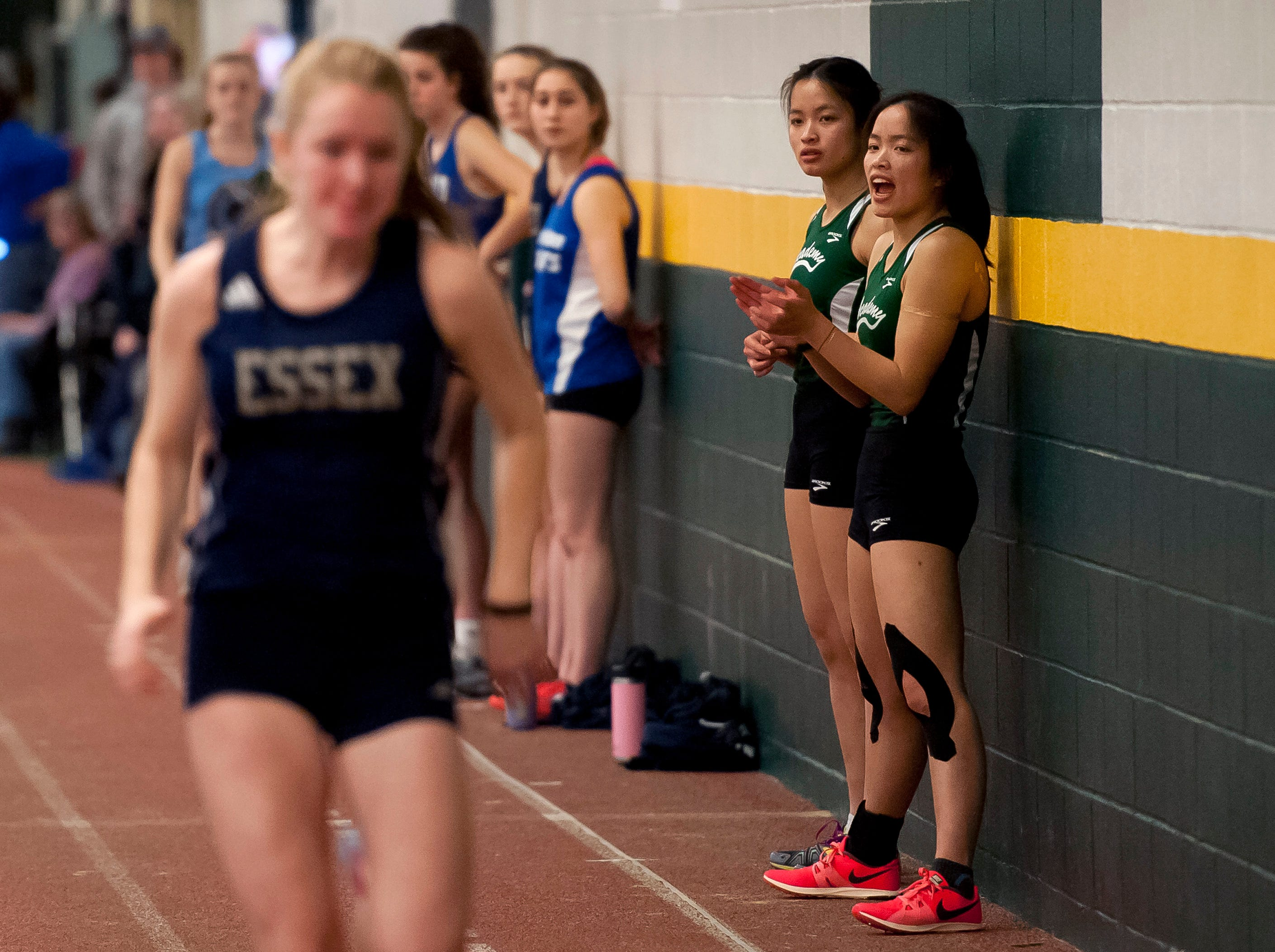 St. Johnsbury twins Lia Rotti, right, and Jen Rotti cheer on the action at the high school indoor track state championships at the University of Vermont on Saturday.