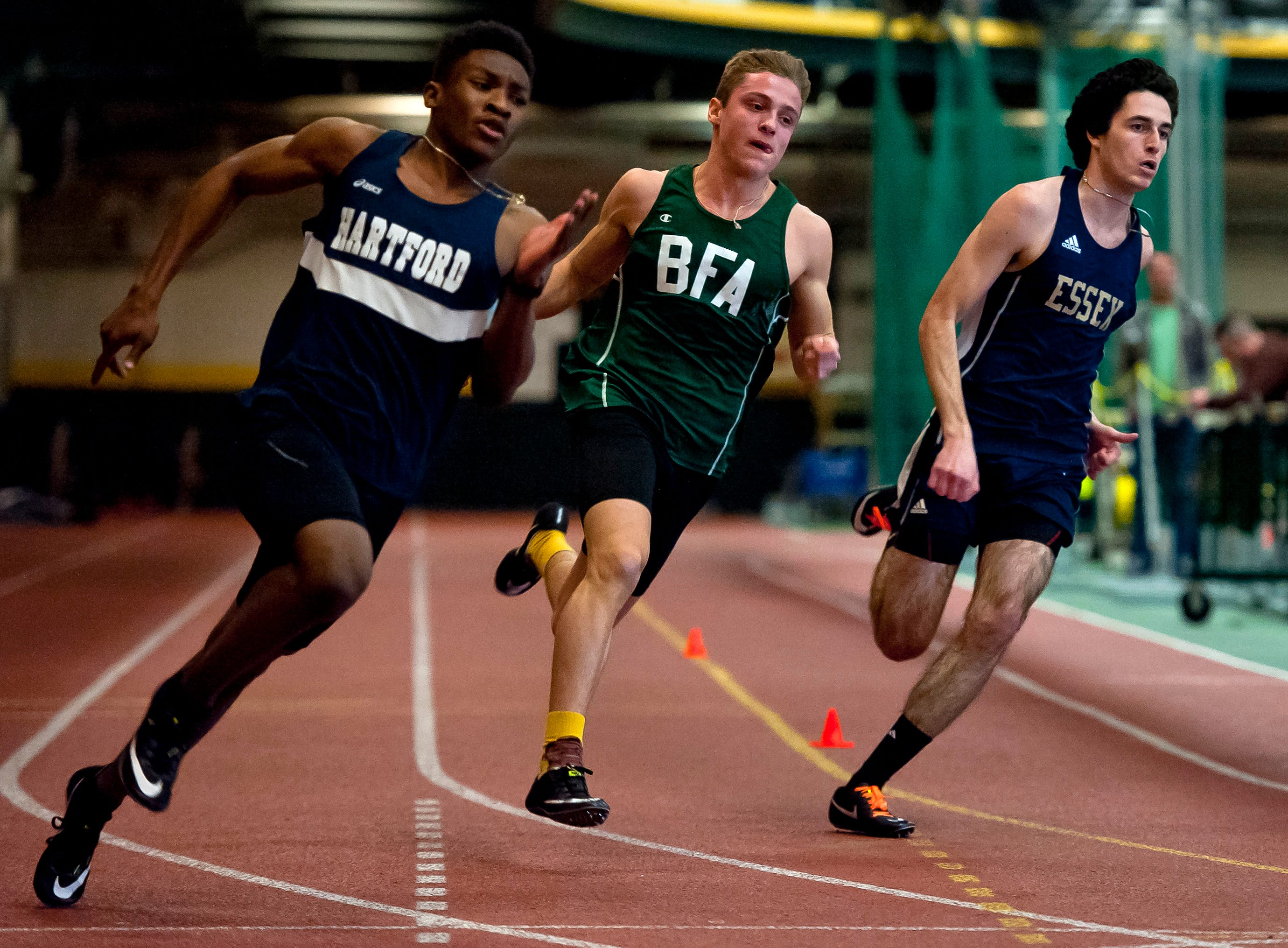 Hartford's Abayomi Lowe, left, BFA-St. Albans' Trey Poquette and Essex's Spencer Towle round a bend in the boys 300 meters at the high school indoor track state championships at the University of Vermont on Saturday.