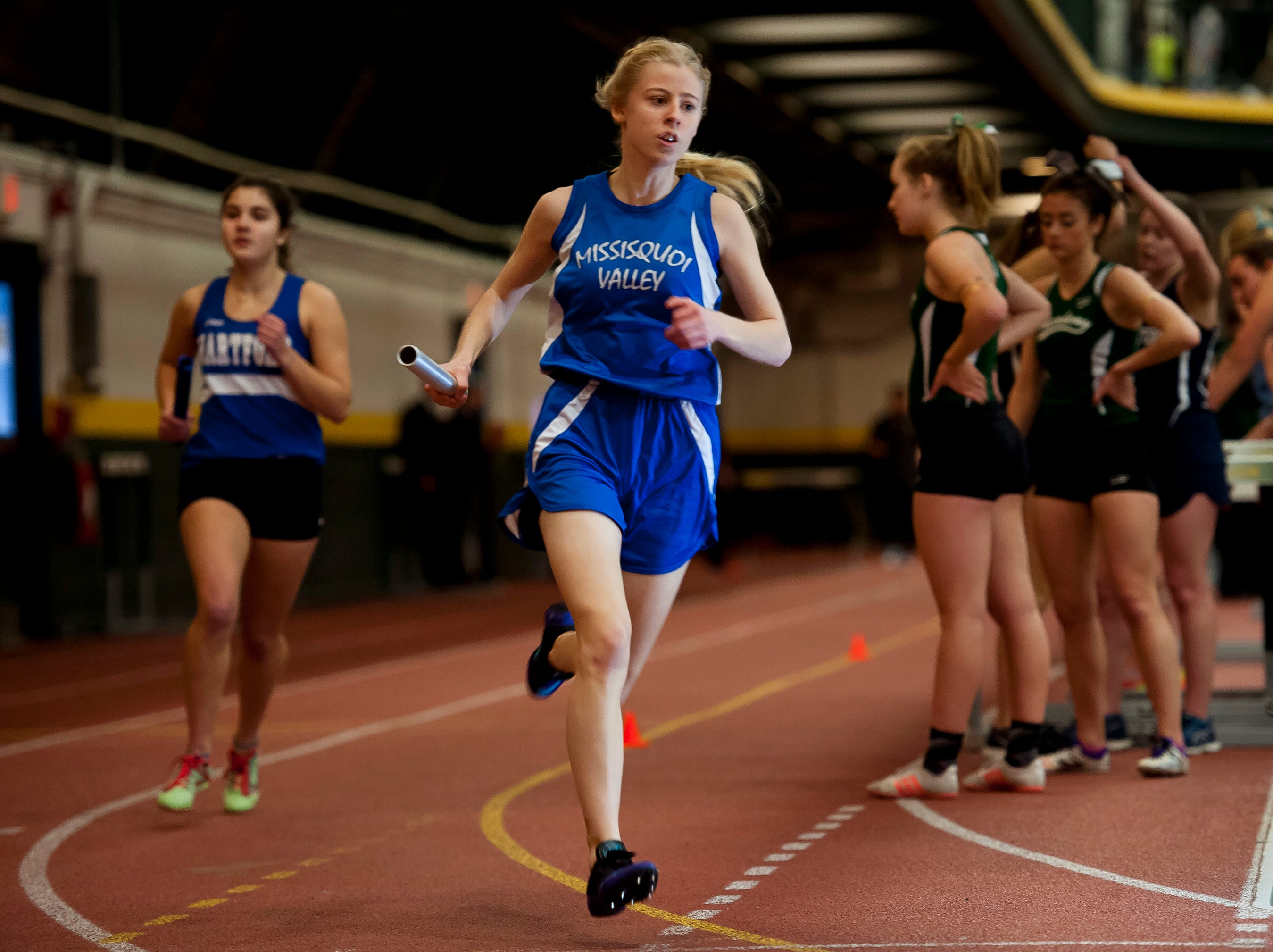Missisquoi's Ruth Brueckner, center, heads into a turn during her leg of the girls 4x800 relay at the high school indoor track state championships at the University of Vermont on Saturday.