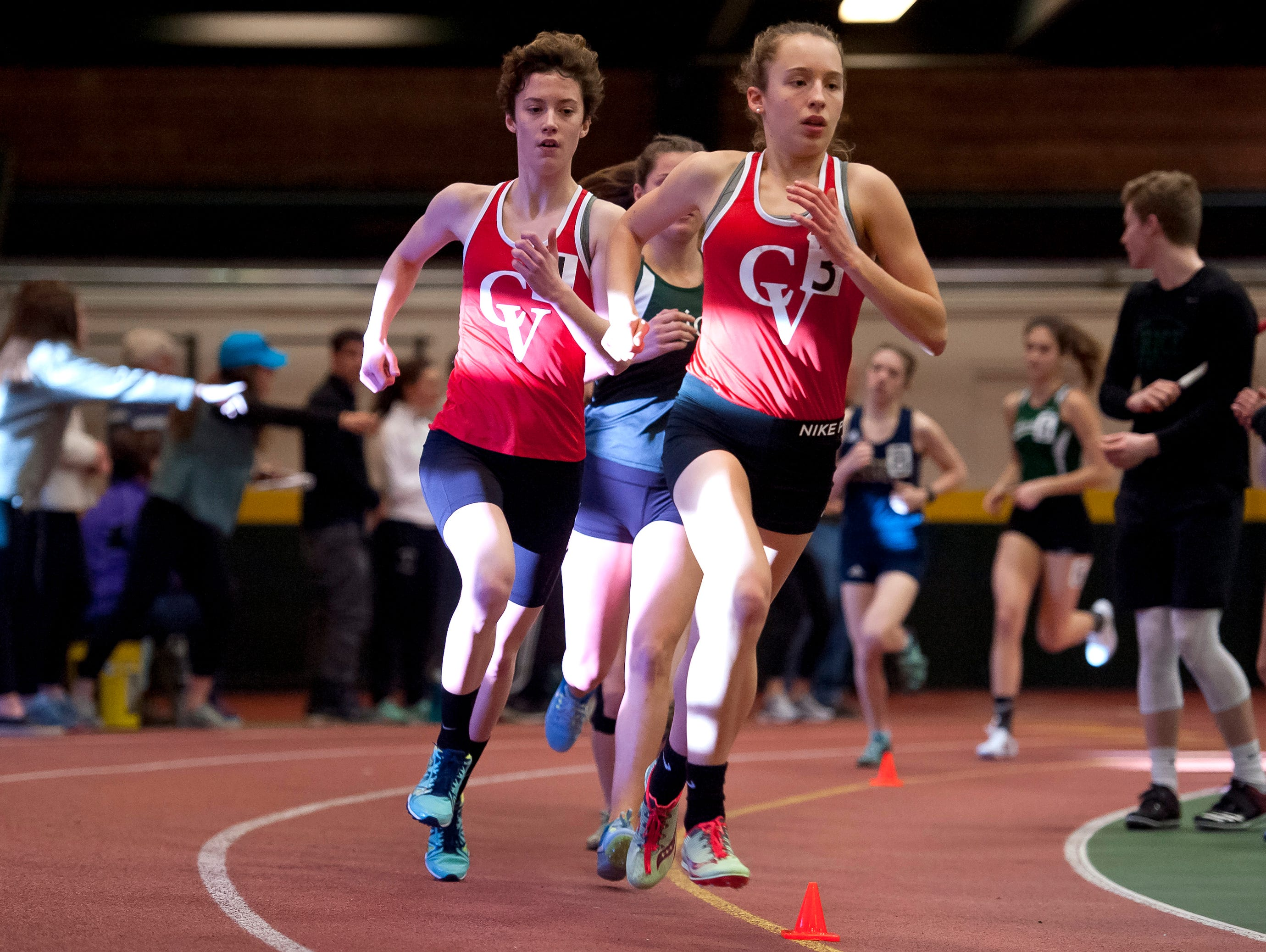 Champlain Valley's Alice Larson, left, and Ella Whitman take a corner in the girls 1,500 meters at the high school indoor track state championships at the University of Vermont on Saturday.