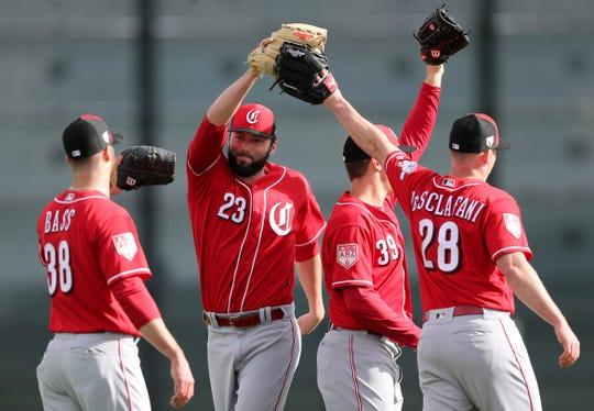 Cincinnati Reds pitcher Cody Reed (23), center, high fives other pitchers at the conclusion of fielding drills, Sunday, Feb. 17, 2019, at the Cincinnati Reds spring training facility in Goodyear, Arizona.