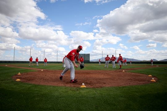Cincinnati Reds pitcher Anthony Bass (38) picks up a baseball during fielding drills, Sunday, Feb. 17, 2019, at the Cincinnati Reds spring training facility in Goodyear, Arizona.
