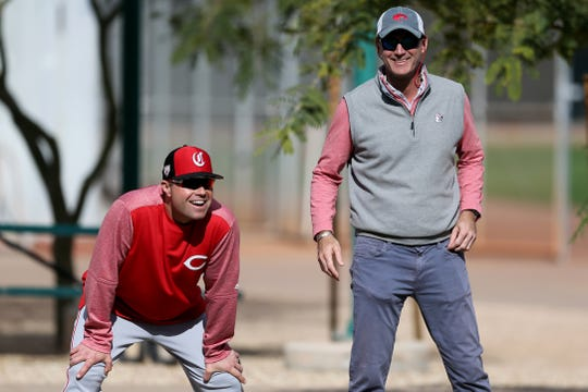 Cincinnati Reds third base/catching coach J.R. House (56), left, and President of Baseball Operations Dick Williams, right, share a laugh as they observe a bullpen session, Sunday, Feb. 17, 2019, at the Cincinnati Reds spring training facility in Goodyear, Arizona.