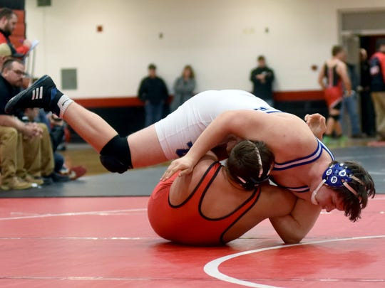 Zanesville's Conner Milner wrestles Coshocton's Thomas Lauvray in the consolation finals at 220 pounds during the East Central Ohio League Tournament on Saturday in Coshocton.