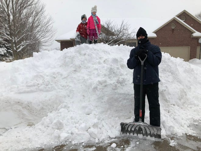 """Mark Tauscheck stands guard as daughter Tenny, 5, and son Ty, 8, lay claim to the """"snow mountain"""" that he and snow plows created in their Clive neighborhood on Sunday, Feb. 17, 2019. #registersnowplay  (Join the fun by Tweeting your best snow photos with the hashtag #registersnowplay)"""