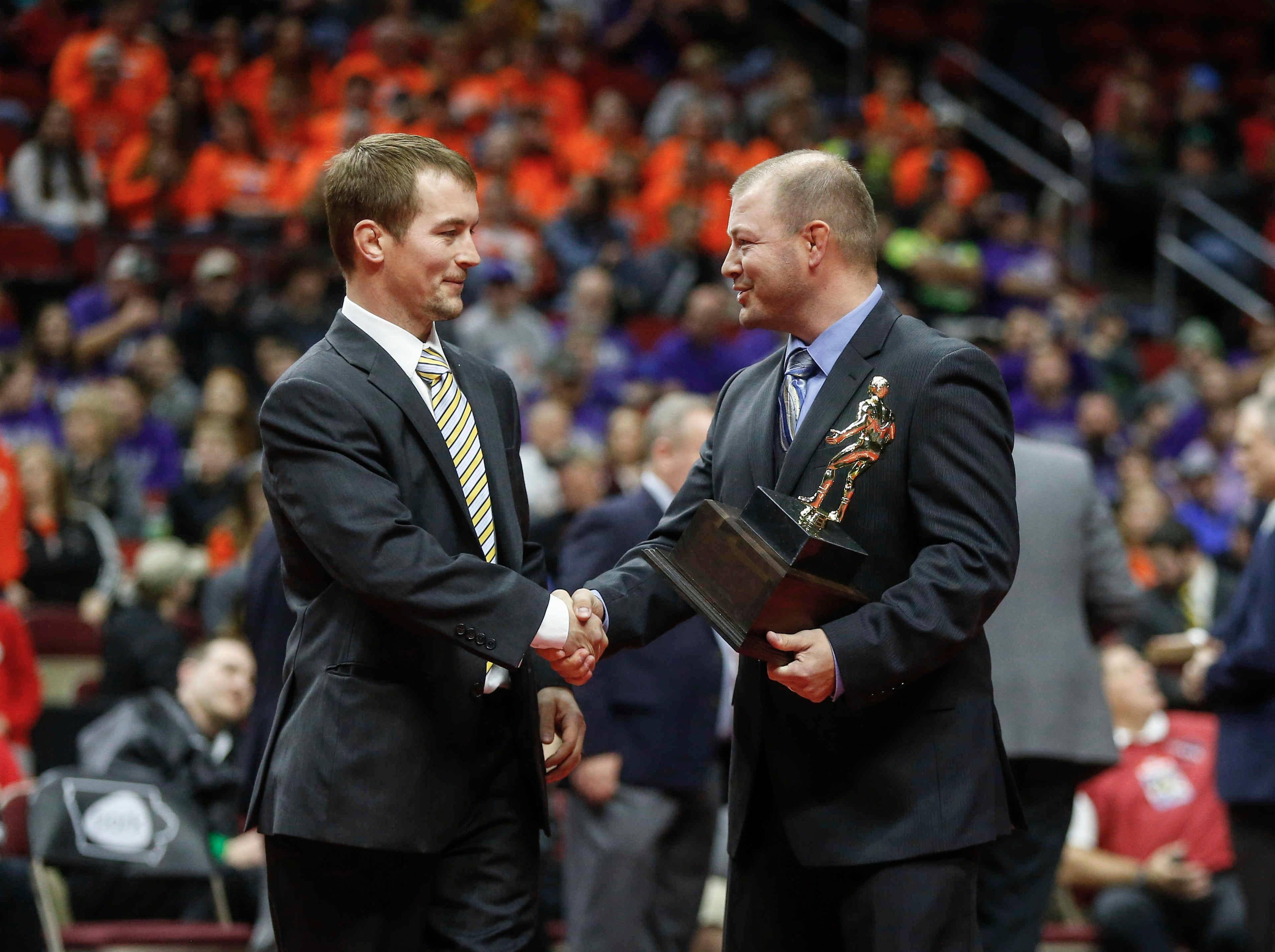 Emmetsburg head wrestling coach Tyler Bjustrom, left, is presented with the Class 1A wrestling coach of the year prior to the start of the state championship wrestling finals on Saturday, Feb. 16, 2019, at Wells Fargo Arena in Des Moines.