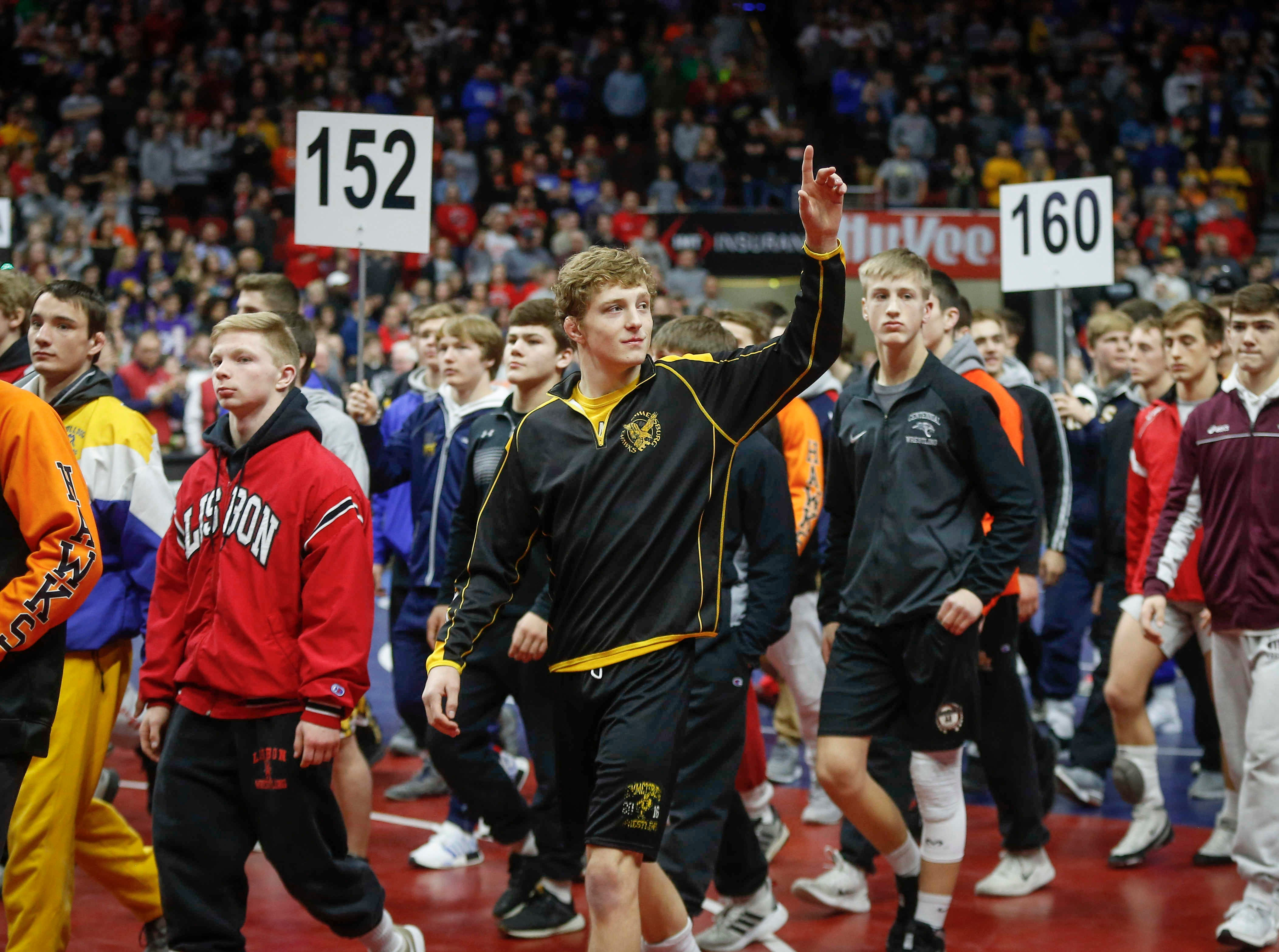 Wrestlers take the mat for the Grand March prior to the start of the 2019 Iowa high school wrestling championship matches on Saturday, Feb. 16, 2019, at Wells Fargo Arena in Des Moines.