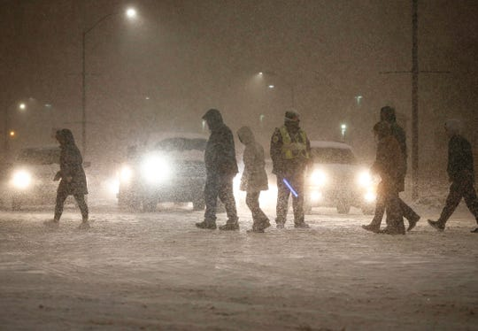 Pedestrians make their way to their cars in driving snow on Saturday following the 2019 Iowa high school state wrestling tournament in Des Moines.