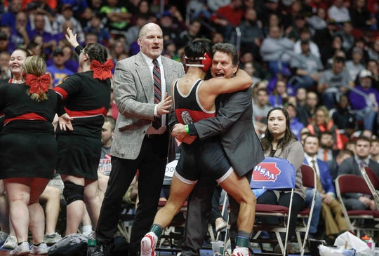 Lisbon coach Brad Smith hugs Robert Avila Jr. after Avila Jr. won the Class 1A state title in 2019 at Wells Fargo Arena in Des Moines. On Thursday, Smith became Iowa's all-time leader in career dual-meet victories.
