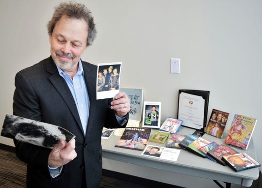In this Thursday, Feb. 7, 2019, Curtis Armstrong, an actor, producer and writer, holds some of the 30-years of memorabilia from his career in film and television at Oakland University in Rochester, Mich. Armstrong, an alumnus of the university, has donated the material to Oakland University's archives.
