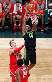Nick Ward said he cut his left hand on this dunk over Ohio State's Justin Ahrens, left, and Andre Wesson during Sunday's first half. Ward said he later injured his hand by hitting it on another player's elbow a few minutes later.