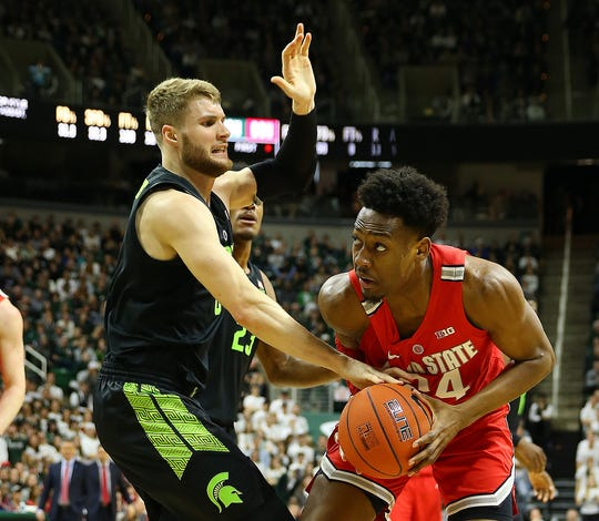 Ohio State forward Andre Wesson attempts to control the ball against Michigan State forward Kyle Ahrens the first half on Sunday, Feb. 17, 2019, in East Lansing.