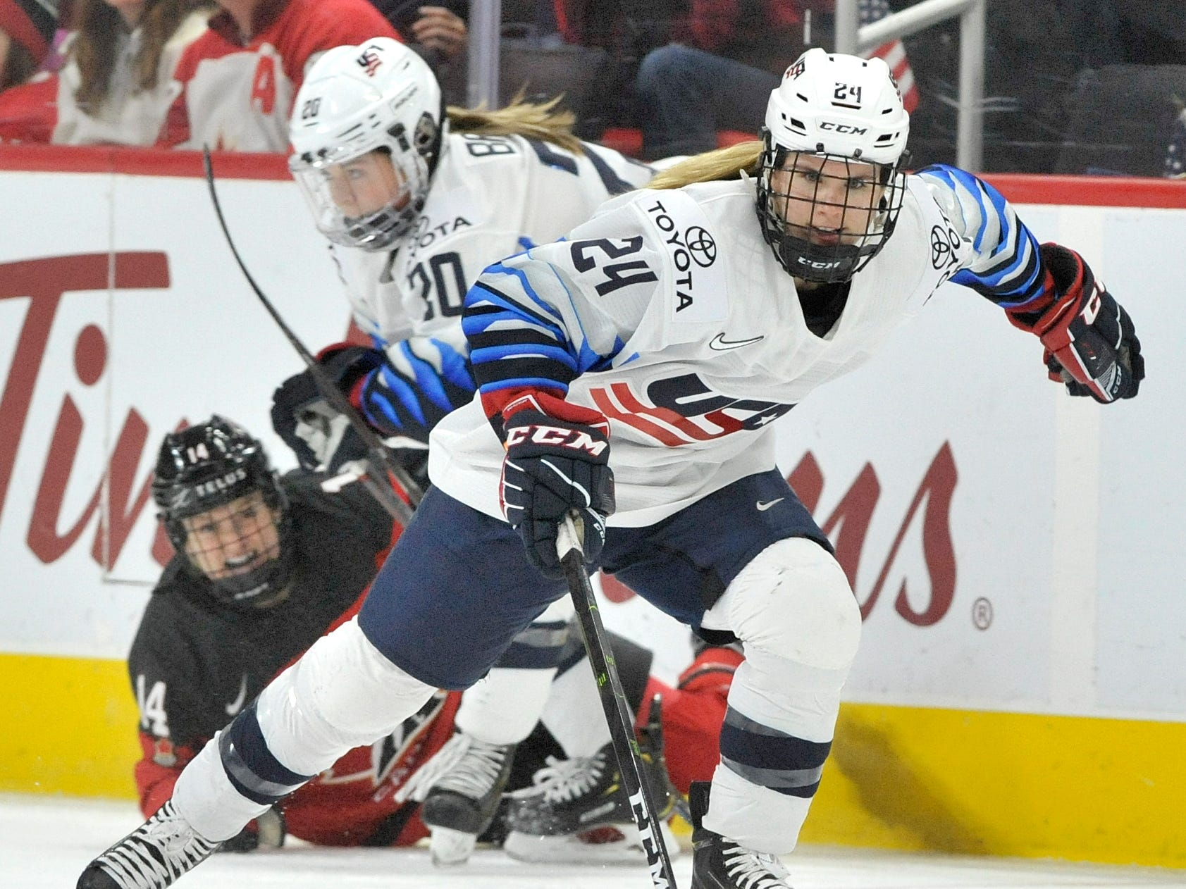U.S's Dani Cameranesi(24) skates away with the puck as teammate Hannah Brandt(20) is tied up with Canada's Renata Fast(14) in the first period.