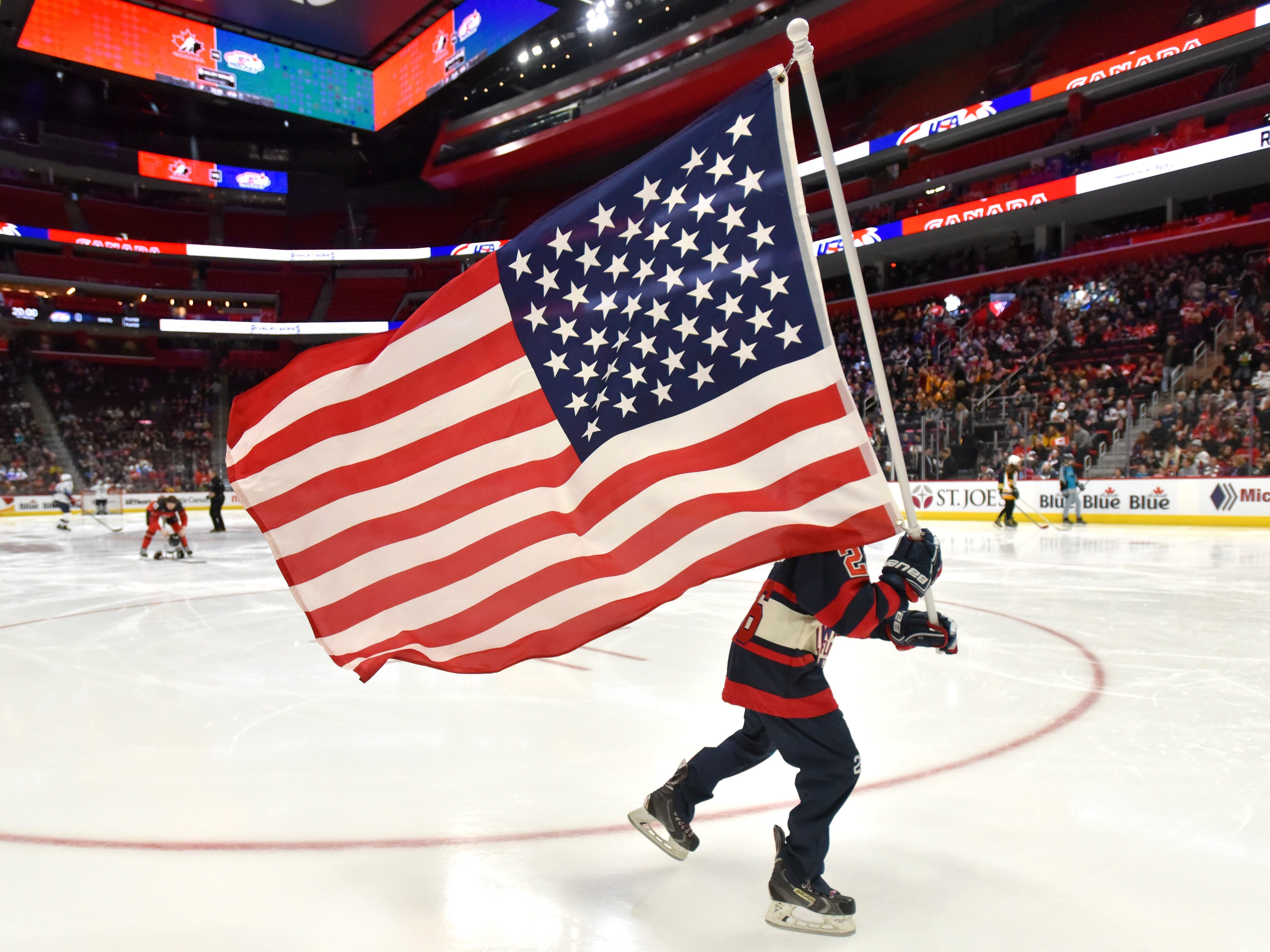 This person skates off the ice with the U.S. flag after Oh Canada and The National Anthem.