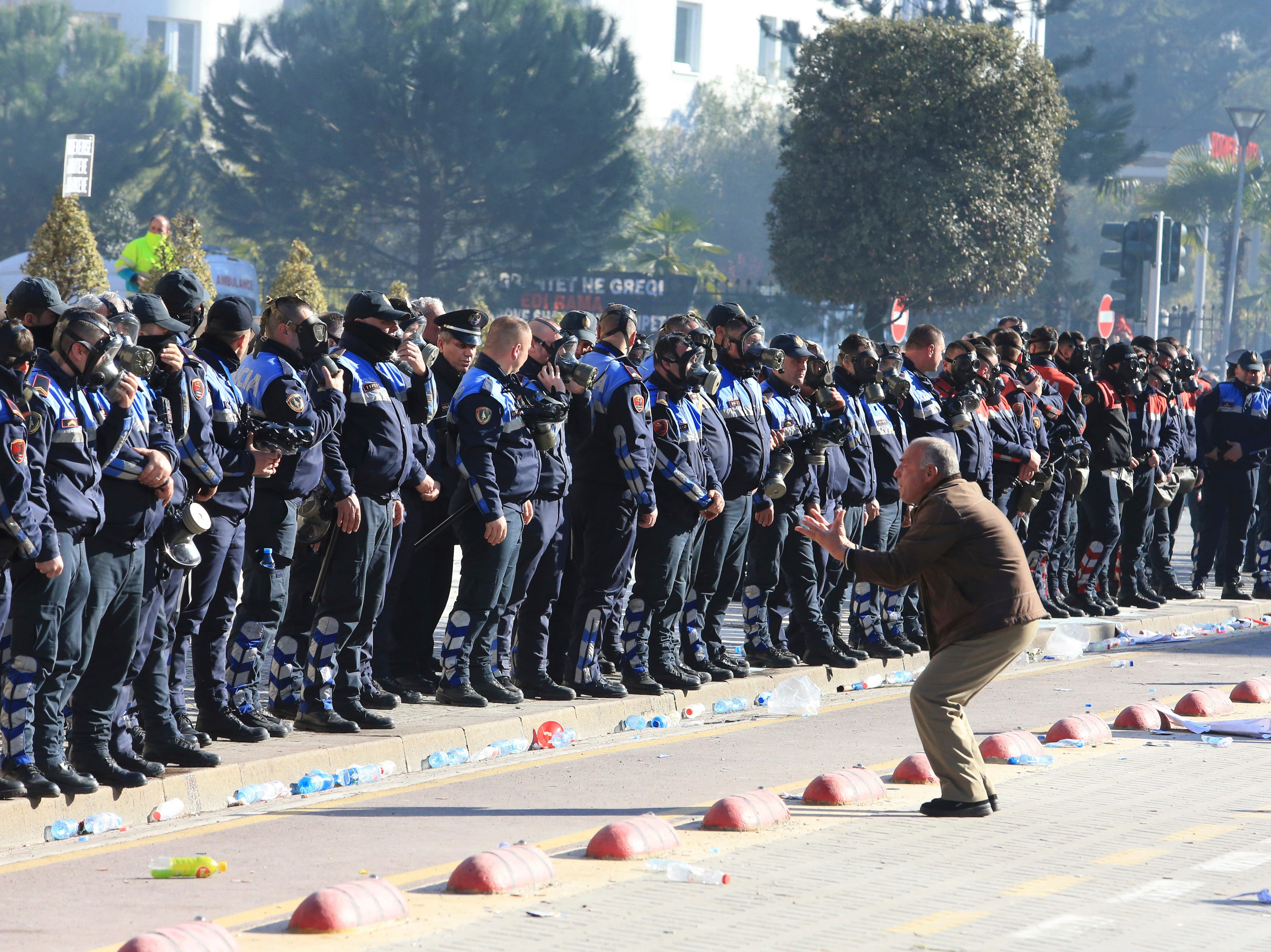 An opposition supporter shouts at police officers during an anti-government rally outside the prime minister's office in the capital Tirana, Albania, Saturday, Feb.16, 2019. Thousands of Albanian opposition supporters have clashed with police in an anti-government rally to protest what they say is a corrupt and inefficient Cabinet, asking for its resignation and early elections.