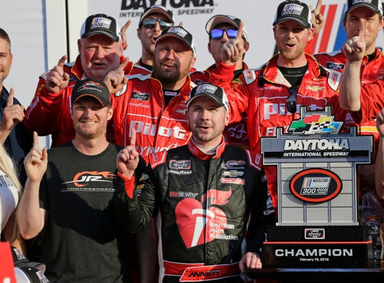 Team owner, Dale Earnhardt Jr., front left, celebrate with NASCAR Xfinity series auto race winner Michael Annett, center front, at Daytona International Speedway.