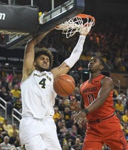 Michigan's Isaiah Livers throws down a dunk over Maryland's Darryl Morsell in Saturday's win.