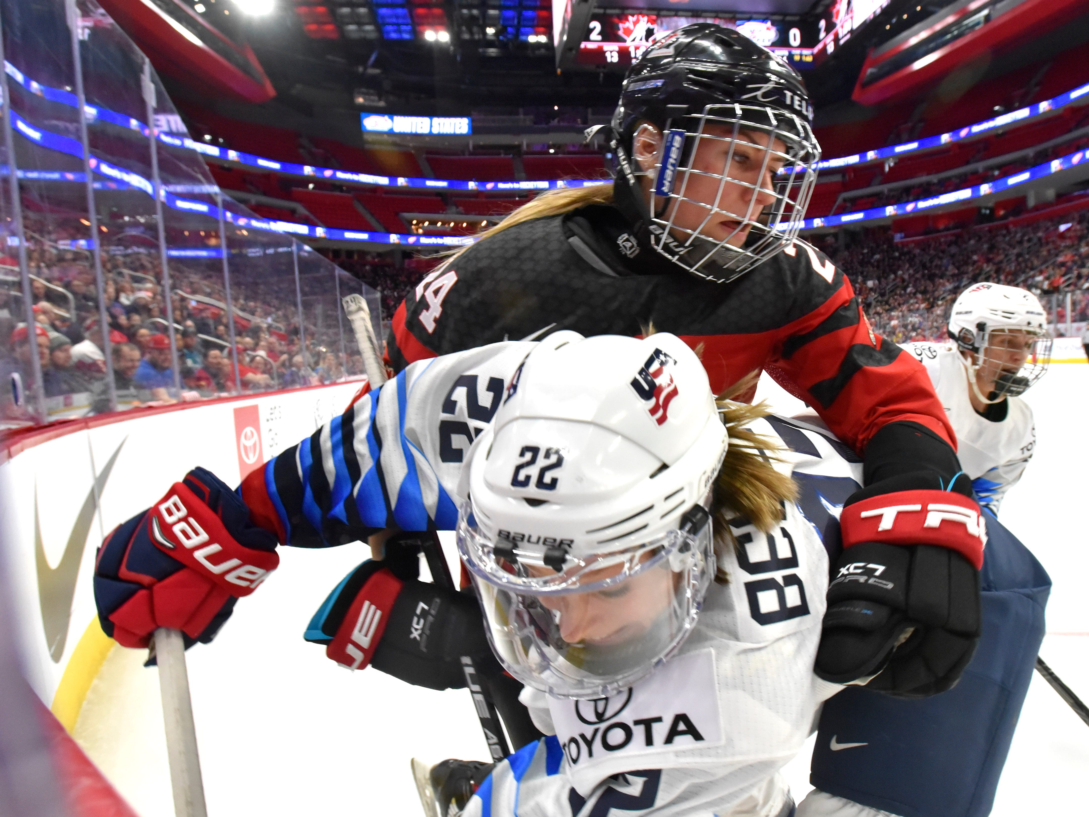 U.S's Kacey Bellamy(22) and Canada's Natalie Spooner(24) tight it up in the corner near the end of the second period.
