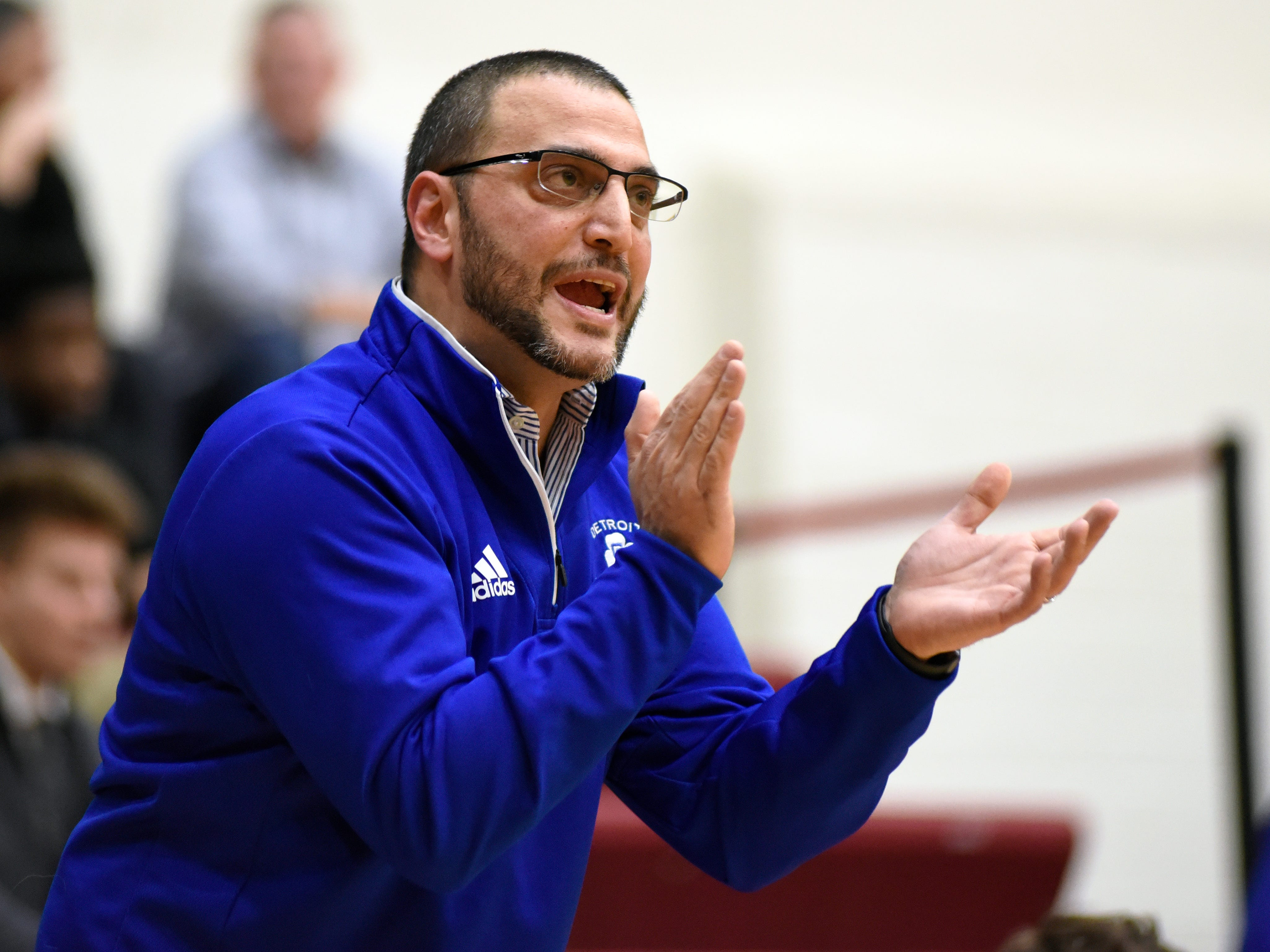 Detroit Catholic Central basketball head coach Brandon Sinawi cheers on his team as they played against Detroit Jesuit during the first quarter.