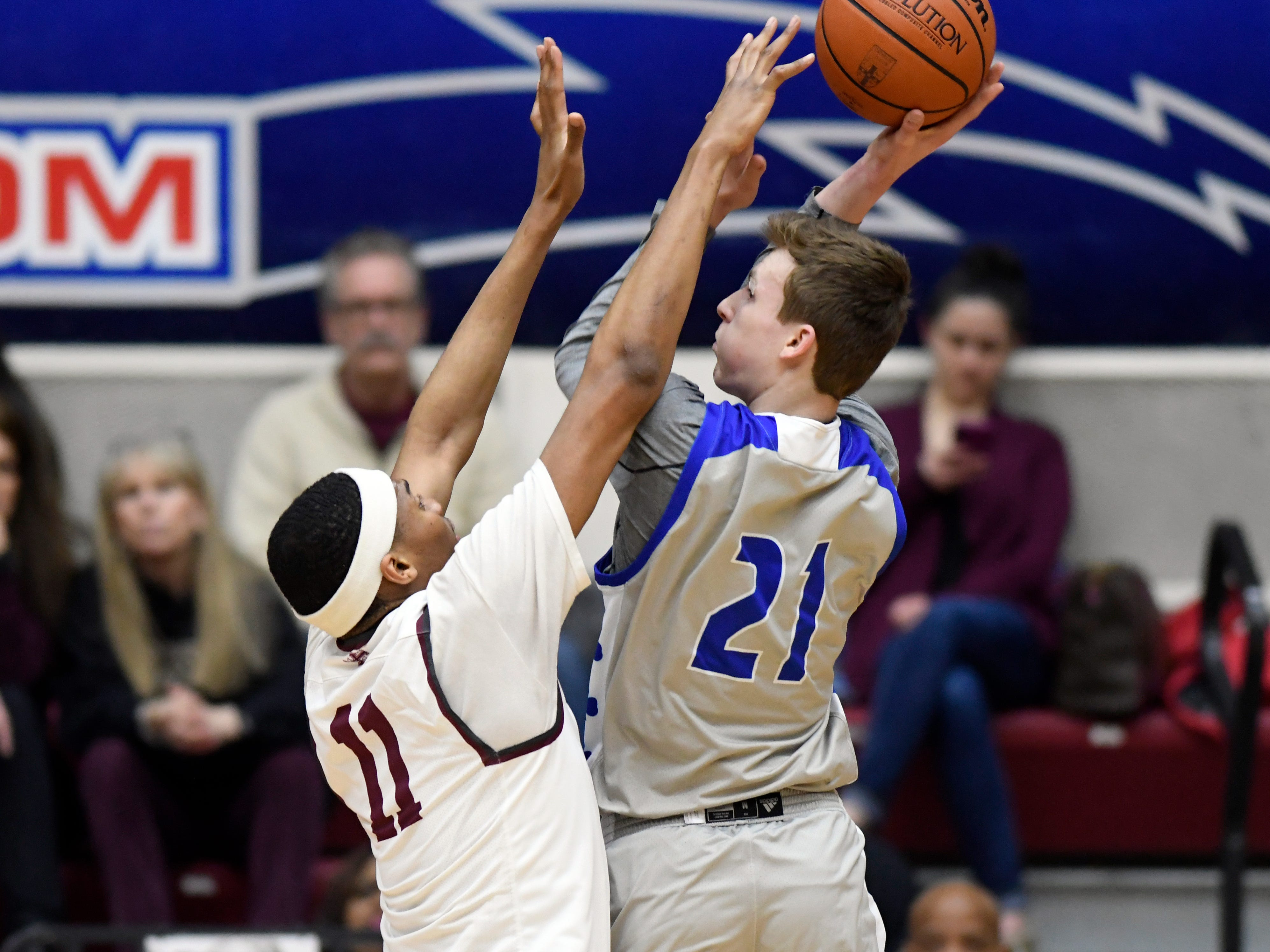 Detroit Catholic Central's Justin Rukat (21) puts up a shot over U. of D Jesuit forward Jalen Thomas (11) during the first quarter, Saturday, Feb. 16, 2019 in a Catholic League A-B Division Final held at Calihan Hall in Detroit. Jesuit defeated Catholic Central 63-54.
