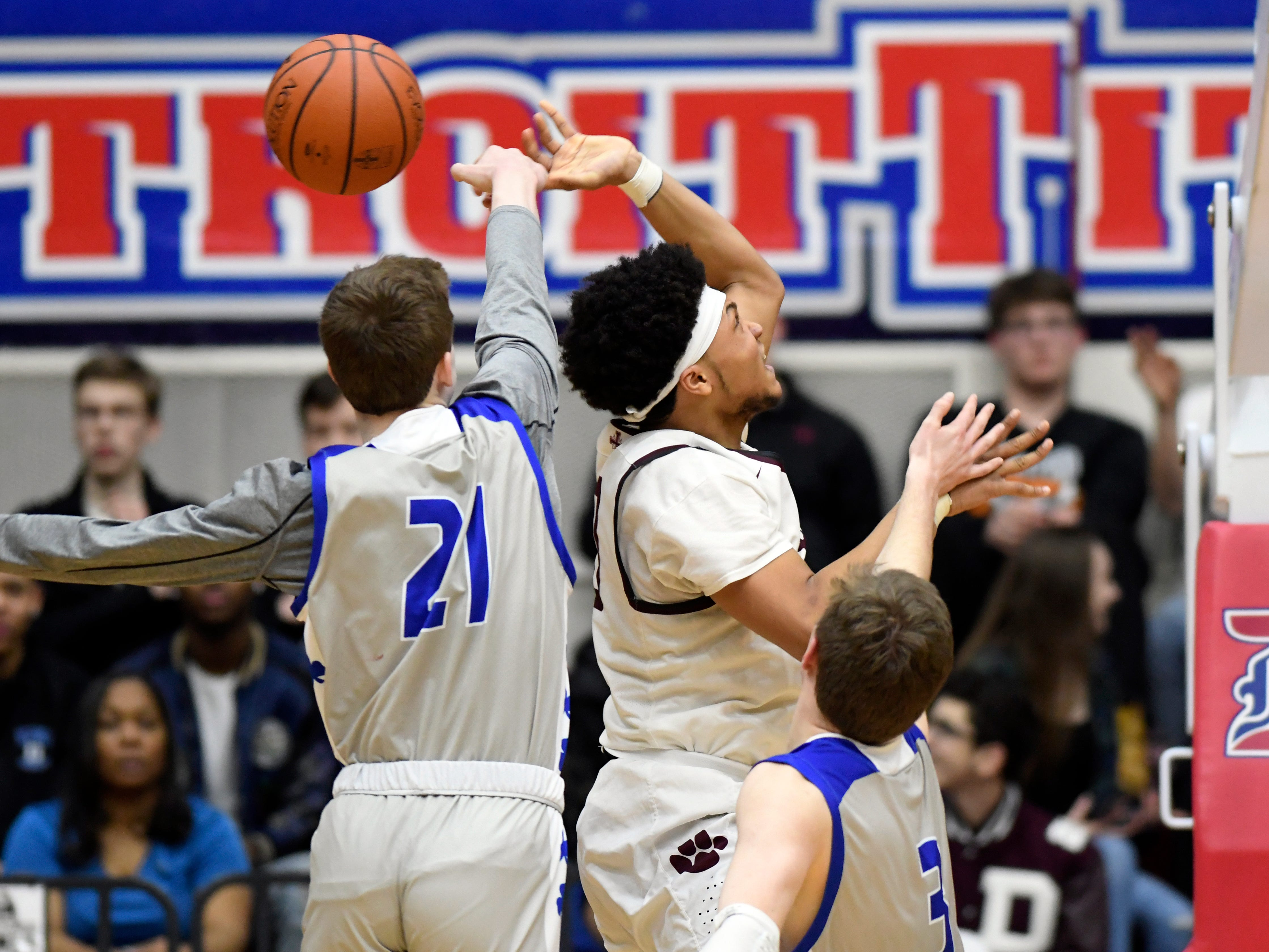 Detroit Catholic Central's Justin Rukat (21), left, knocks the ball away from U. of D Jesuit guard Daniel Friday (0) during the third quarter.