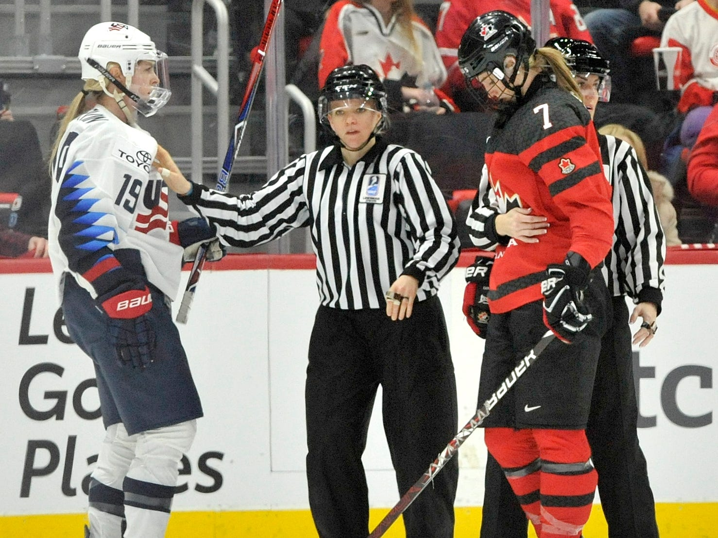 Referees separate Gigi Marvin(19) and Canada's Laura Stacey(7) in the second period.