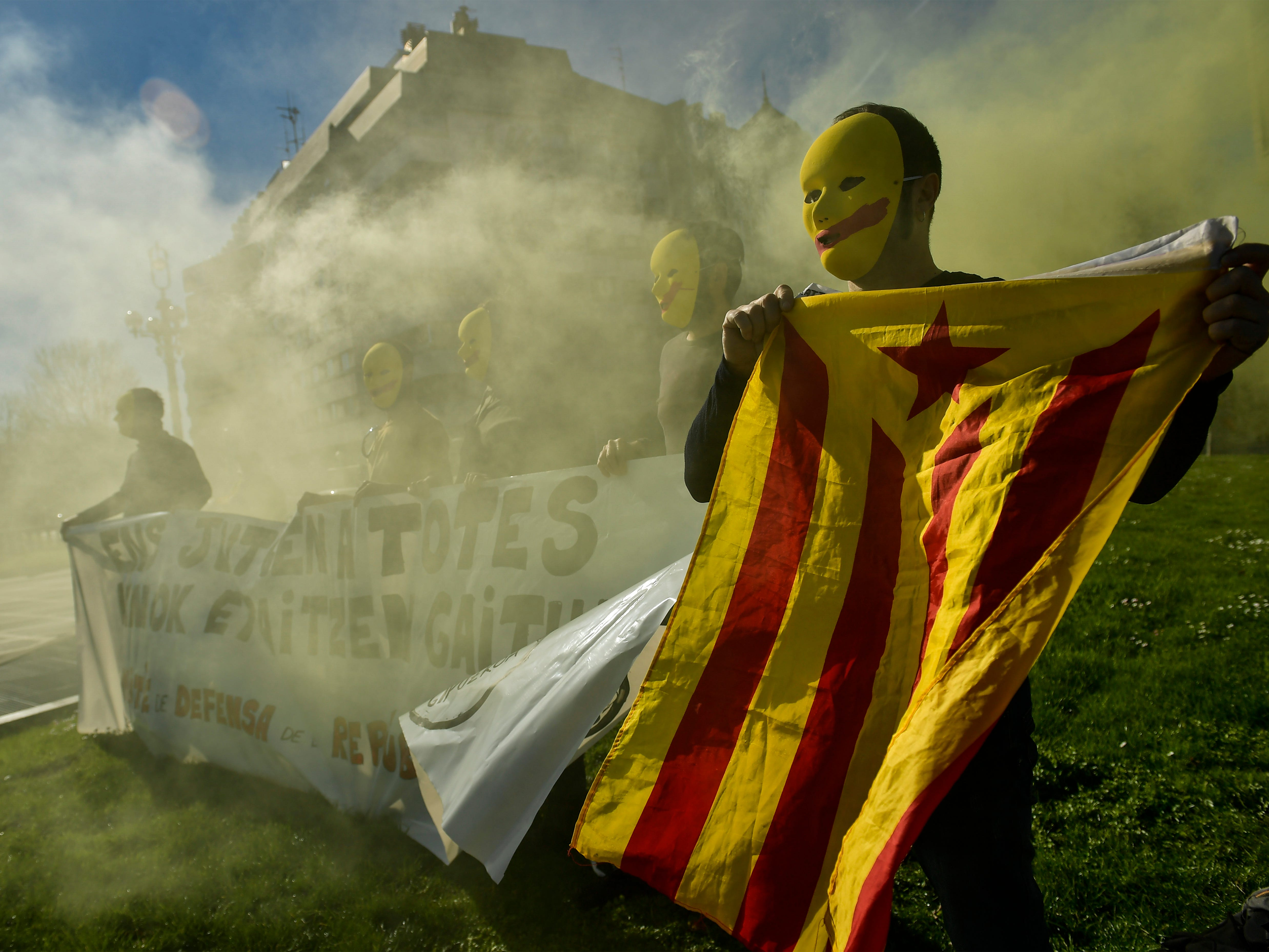 Pro-independence masked demonstrators, one displaying an estelada or independence flag, march during a demonstration supporting the imprisoned pro-independence political leaders in the basque city of San Sebastian, northern Spain, Sunday Feb. 17, 2019.