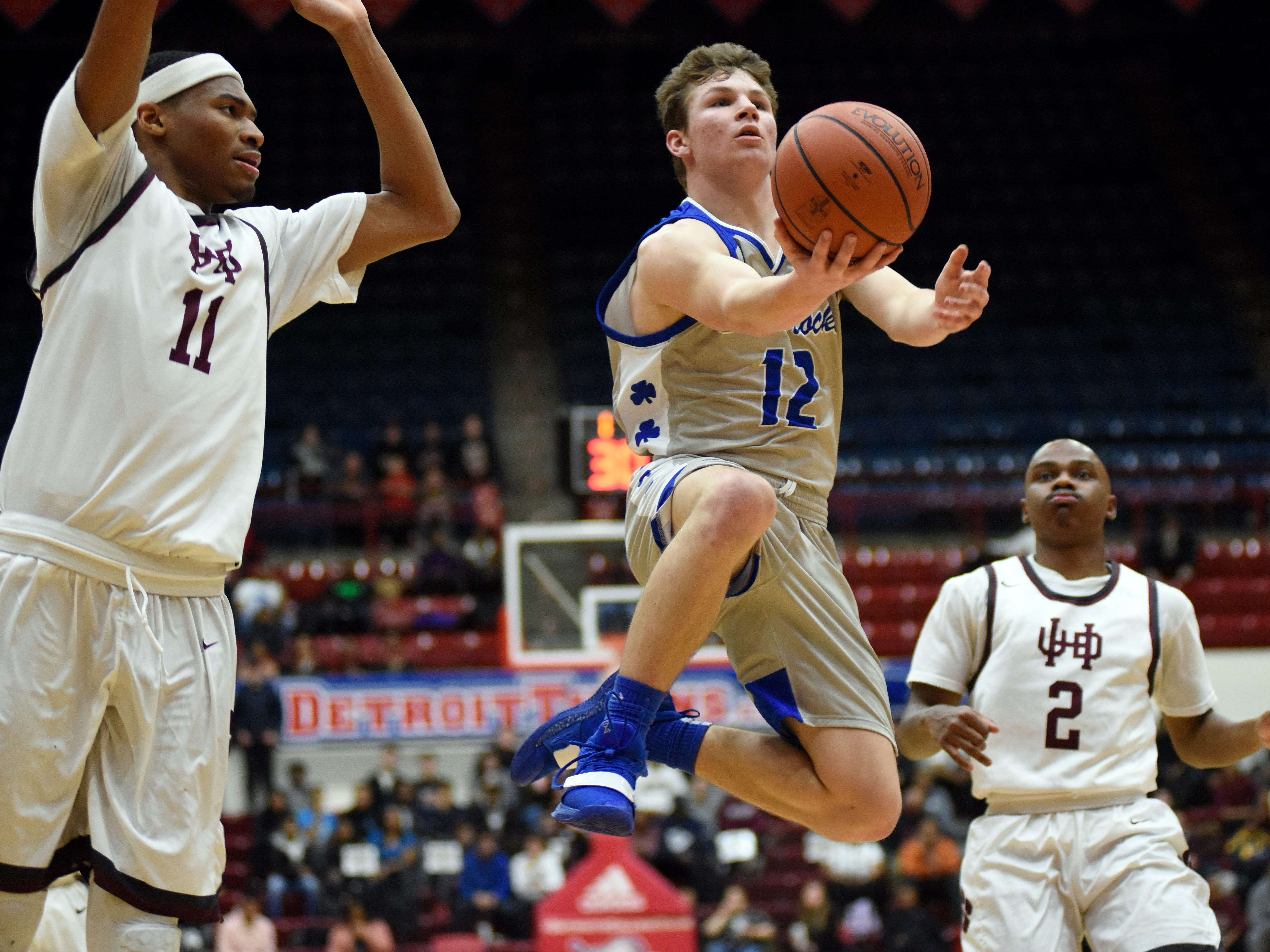 Detroit Catholic Central's Keegan Koehler (12) goes in for a layup in between U. of D Jesuit forward Jalen Thomas (11), left, and guard Caleb Hunter (2) during the third quarter.