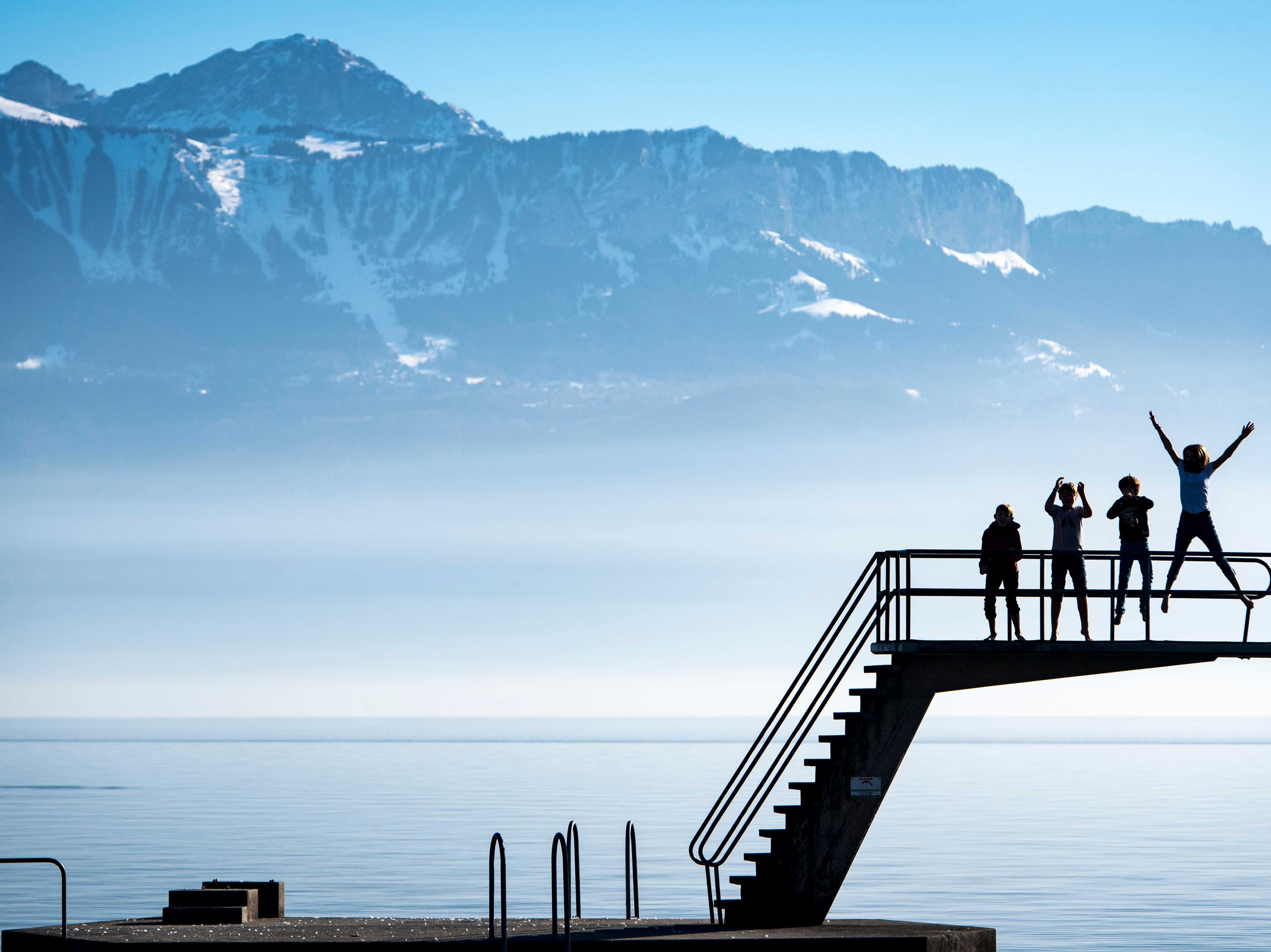 Kids enjoy the sunny and warm weather on a diving platform on the shore of the Lake Geneva in front of the Swiss and French Alps on a unusually warm winter day, in Lutry, Switzerland, Saturday, Feb. 16, 2019.