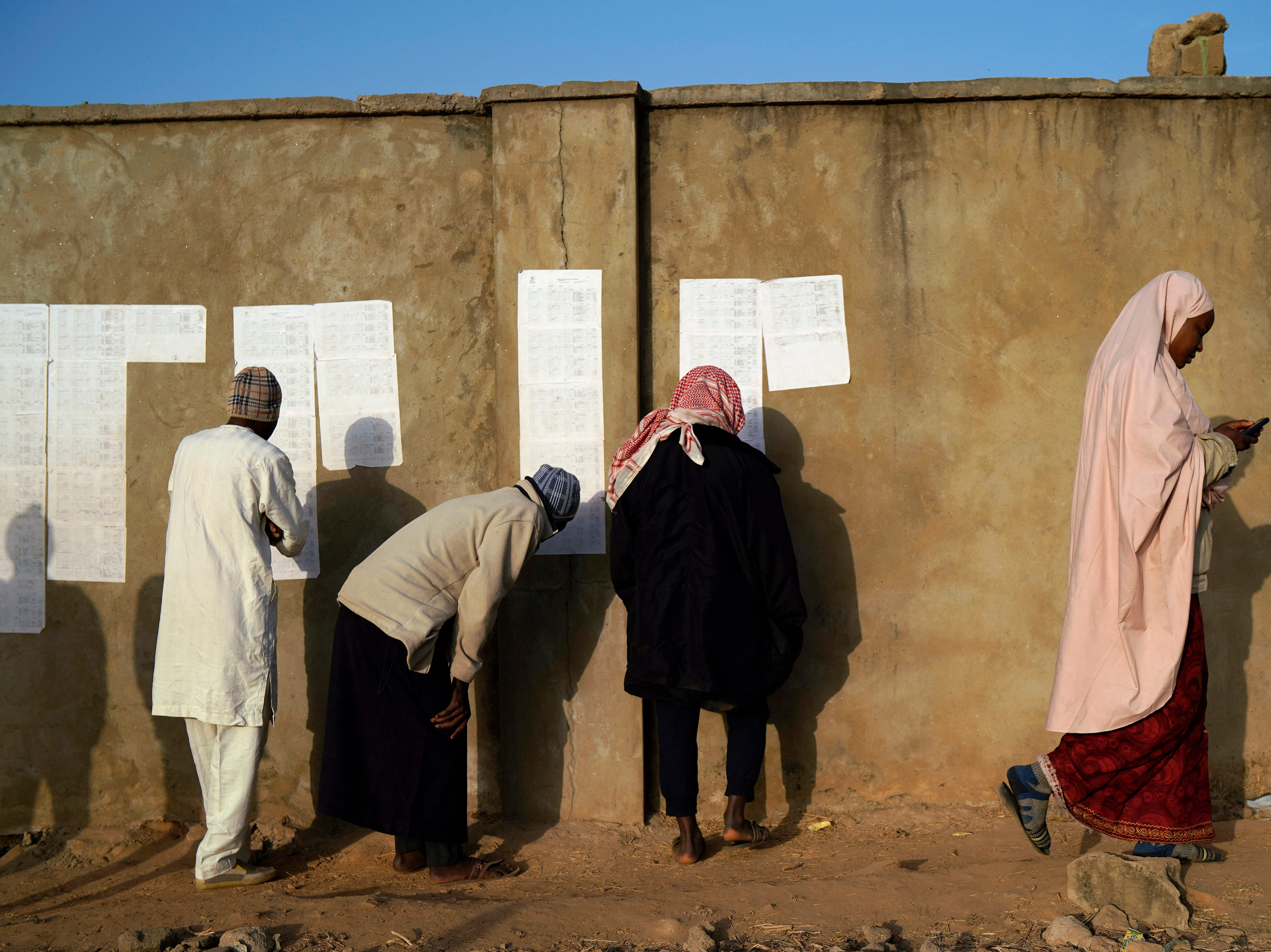 Nigerians check voters' lists at a polling station in Kaduna, Nigeria, Saturday, Feb. 16, 2019. Nigeria's electoral commission delayed the presidential election until Feb. 23, making the announcement a mere five hours before polls were set to open.